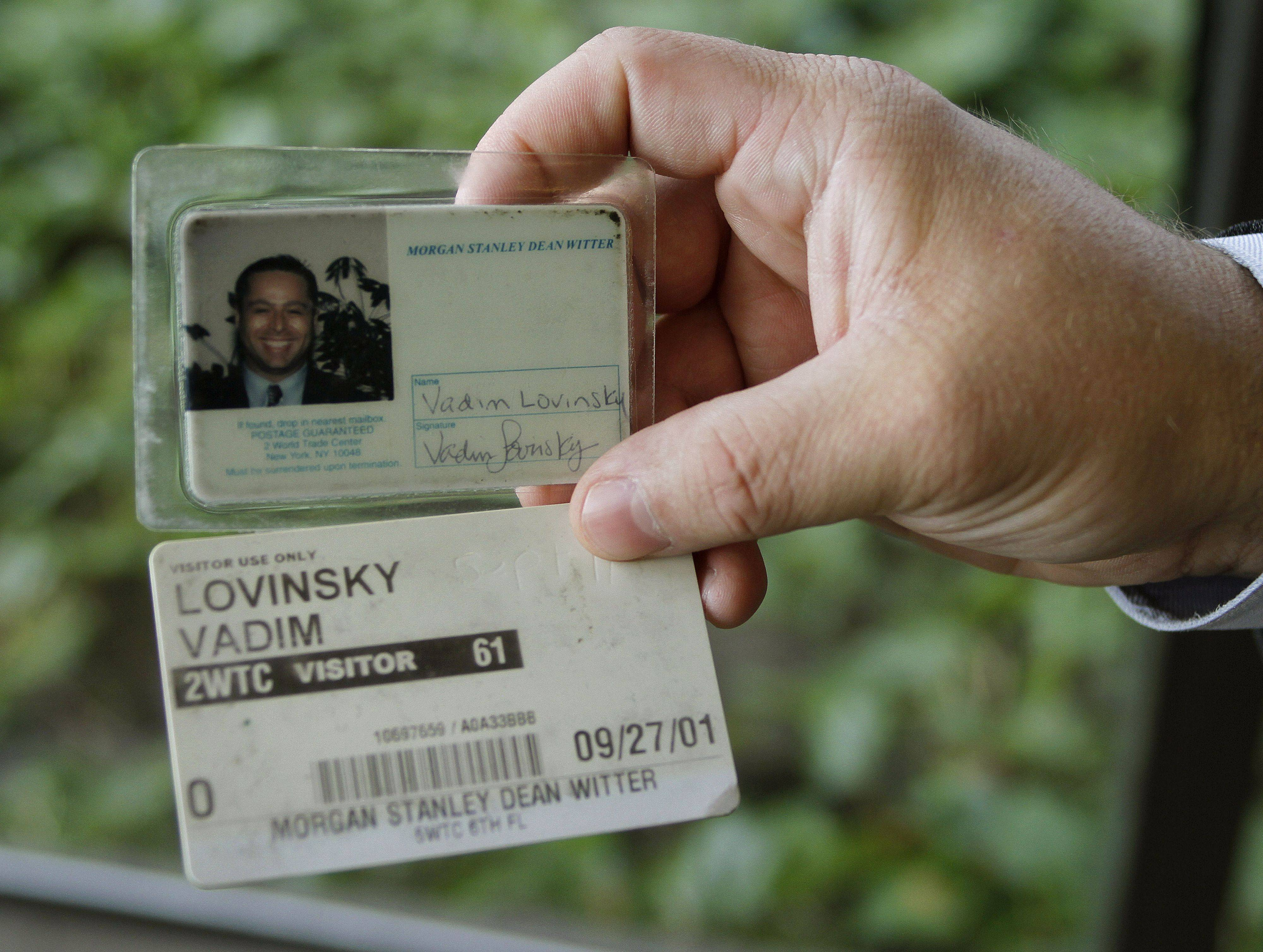 Lovinsky holds up his ID cards from the World Trade Center.