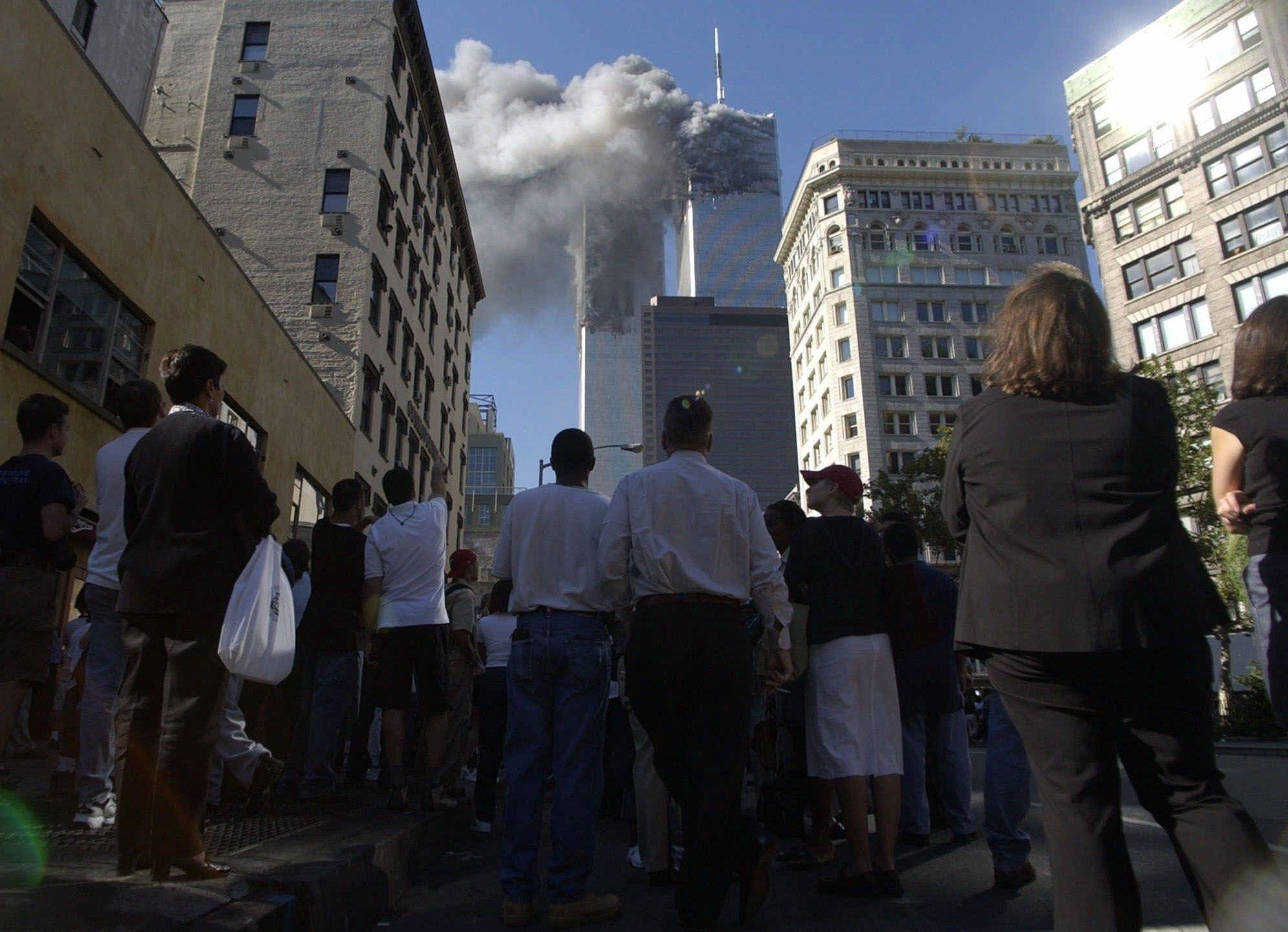 Pedestrians in lower Manhattan watch smoke rise from the World Trade Tower after the early morning terrorist attack on the New York landmark. Television brought the 2001 attacks to the world in real time, and forever linked the thousands who lived through it and the millions who watched.