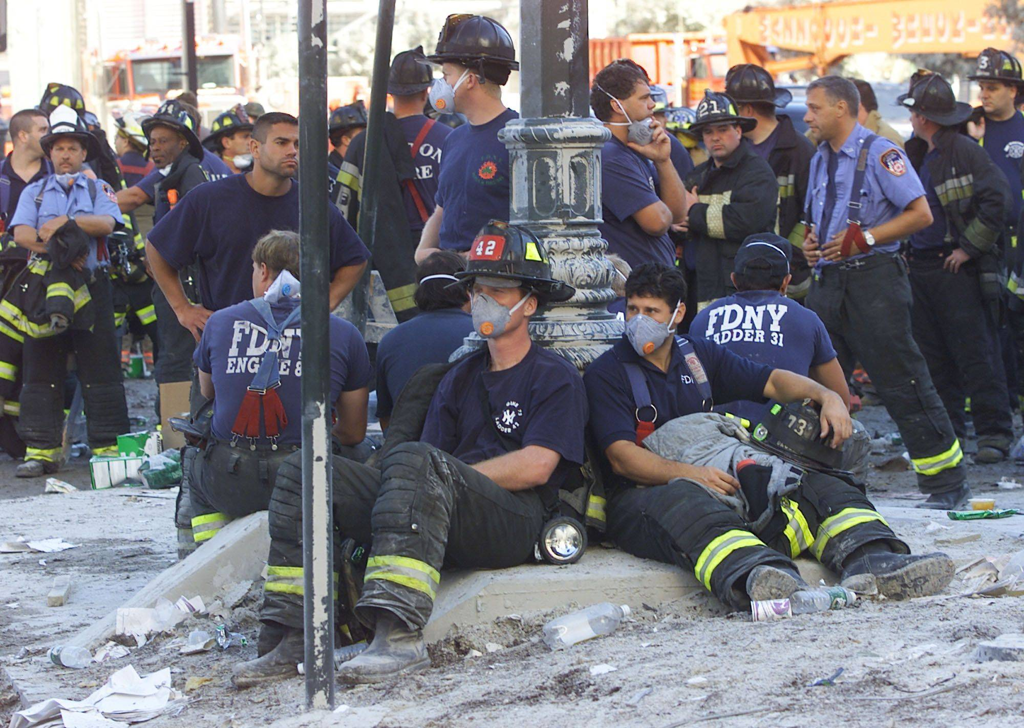 Firefighters rest as rescue efforts continue at the World Trade Center in New York on Sept. 12, 2001.