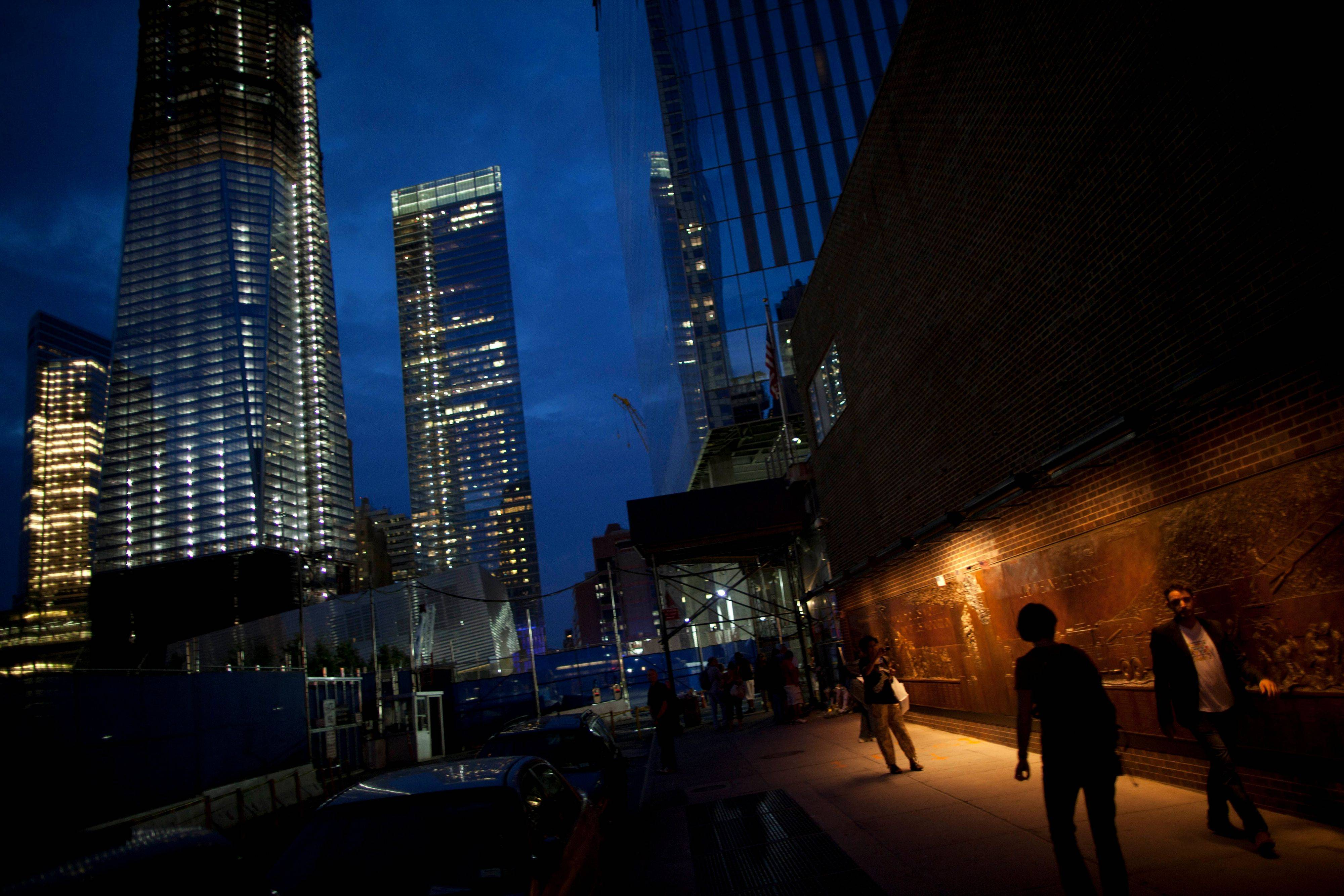 People walk past a memorial for firefighters, right, by the ground zero construction site in New York. Ten years after the 9/11 attacks, New York's prevailing mood is to resist the city's natural tides of forgetting, of moving on.