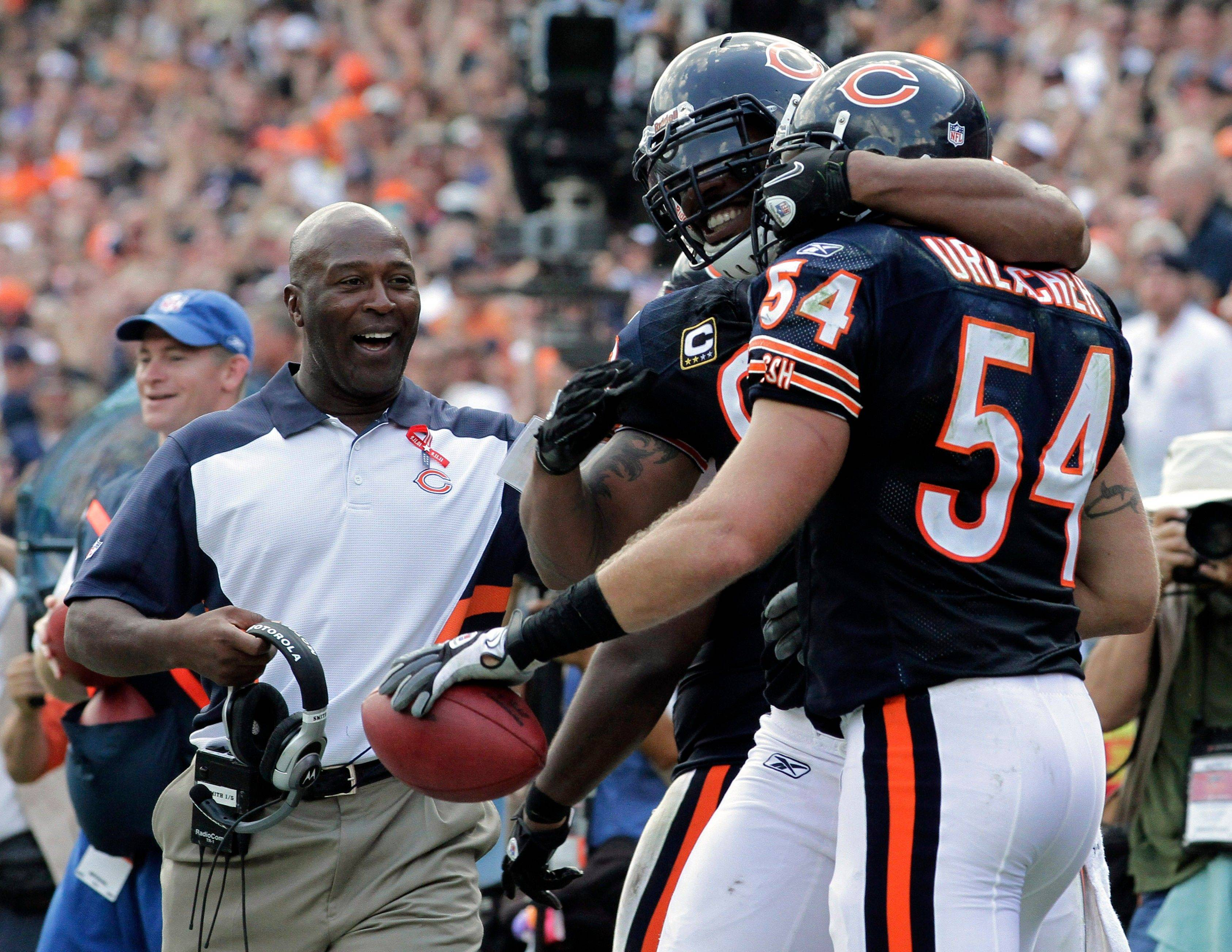 Bears linebacker Brian Urlacher (54) celebrates his fumble recovery and touchdown with teammate Julius Peppers and head coach Lovie Smith, left, in the second half of an NFL football game against the Atlanta Falcons in Chicago, Sunday, Sept. 11, 2011.