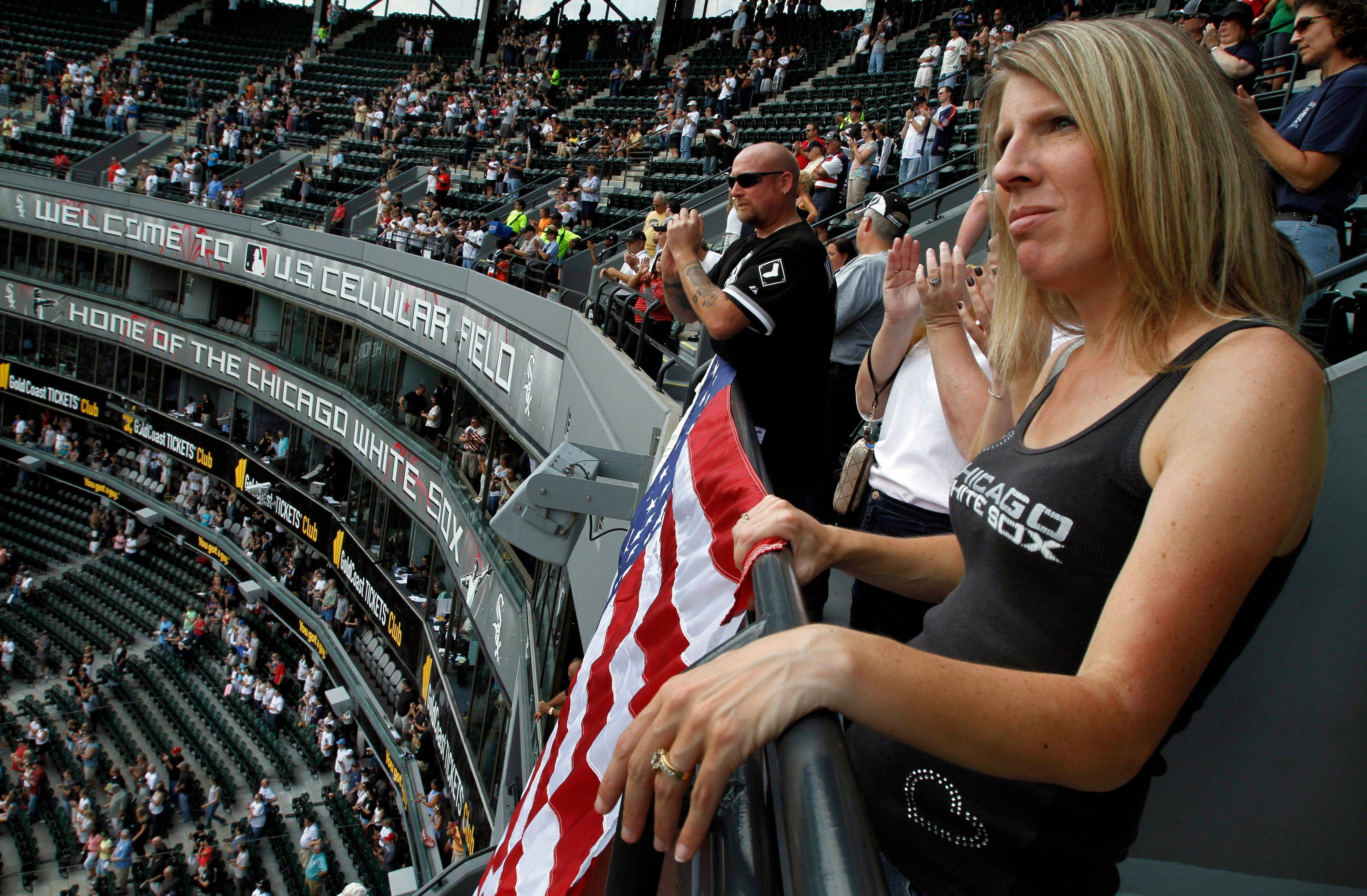 Jen Gurschke, right, and husband Scott unfurl a United States flag during a 9/11 remembrance ceremony Sunday before the start of the White Sox/Indians game at U.S. Cellular Field.