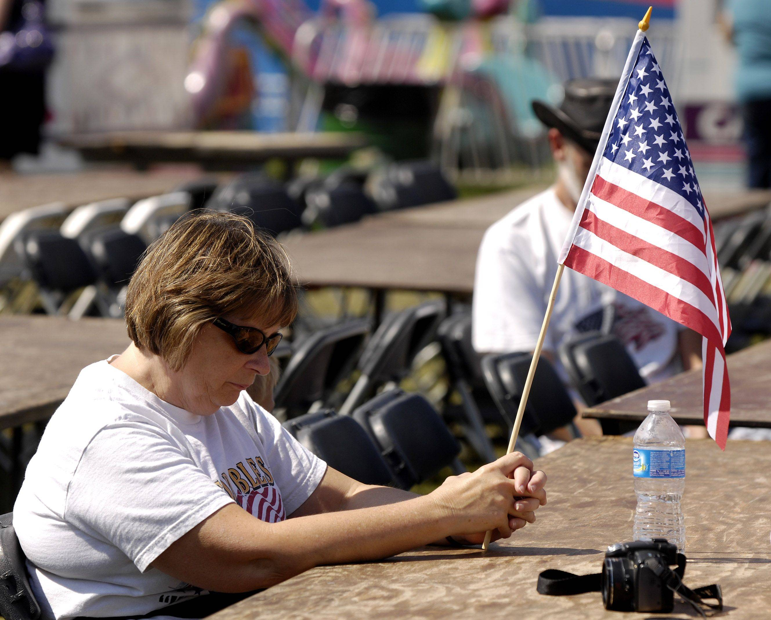 Cindy Matuszak of Bensenville bows her head during a moment of silence at the Villa Park September 11th Anniversary Commemoration Ceremony Sunday.