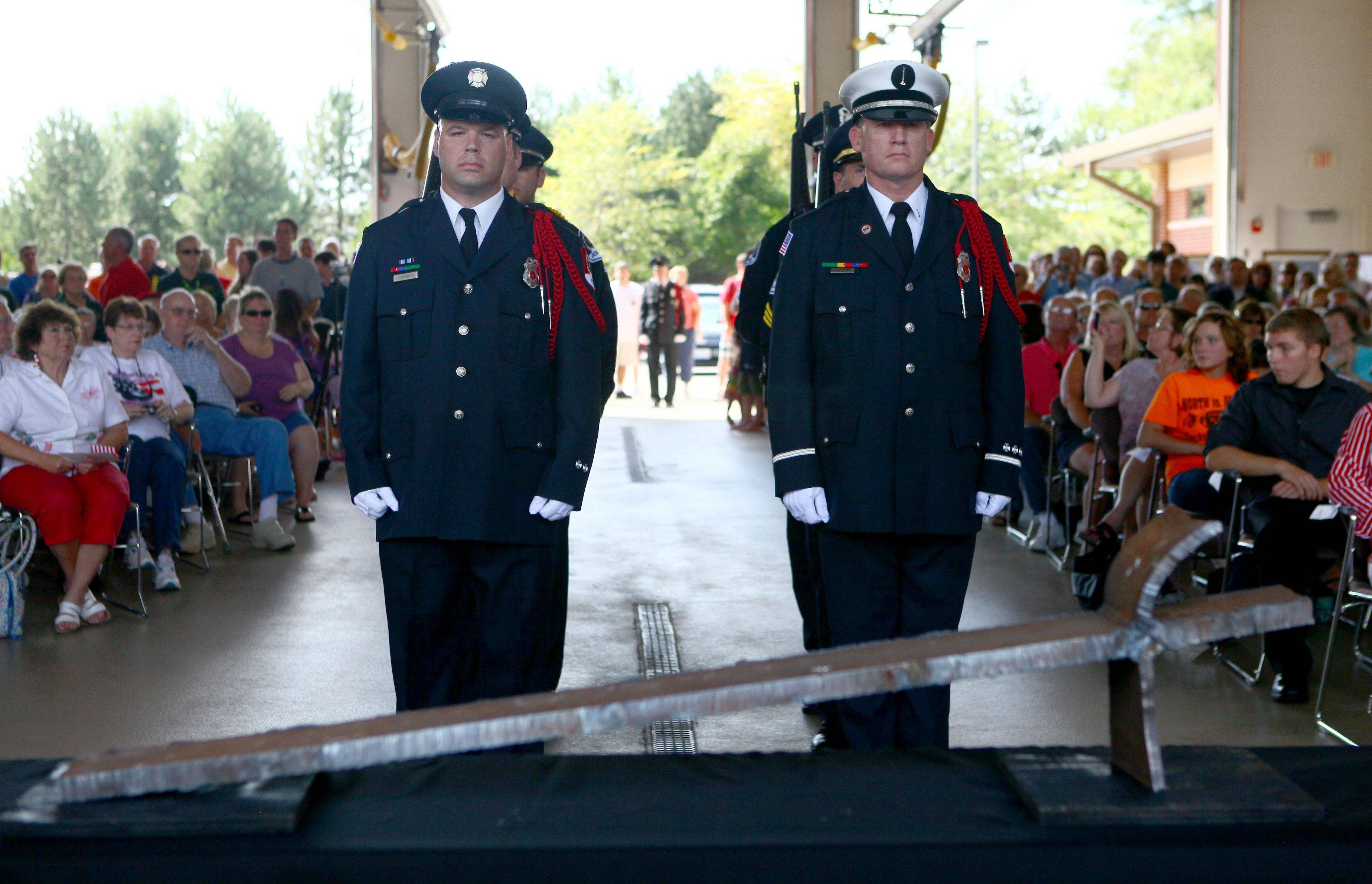 Firefighters Jeremy Lockwood, left, and Phil McGuire, stand in front of the piece of steel taken from the World Trade Center rubble during a 9/11 10th anniversary ceremony Sunday in Mundelein.