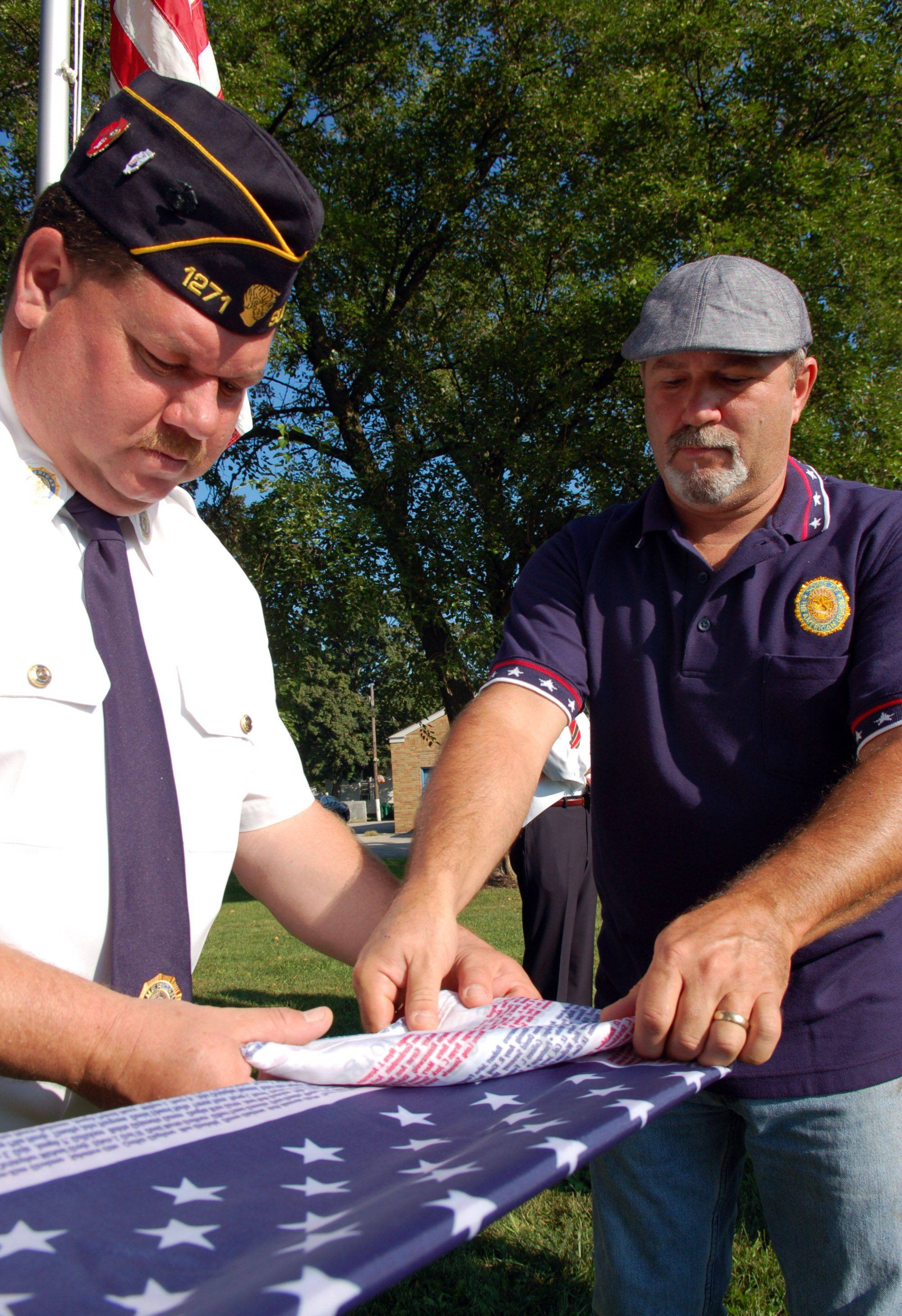"Matt McCannon of Sugar Grove, left, and Mike Carter of Sugar Grove, right, fold the Flag of Honor during the Sugar Grove American Legion ""Remembrance of 9/11"" Sunday at Veterans Park in Sugar Grove."