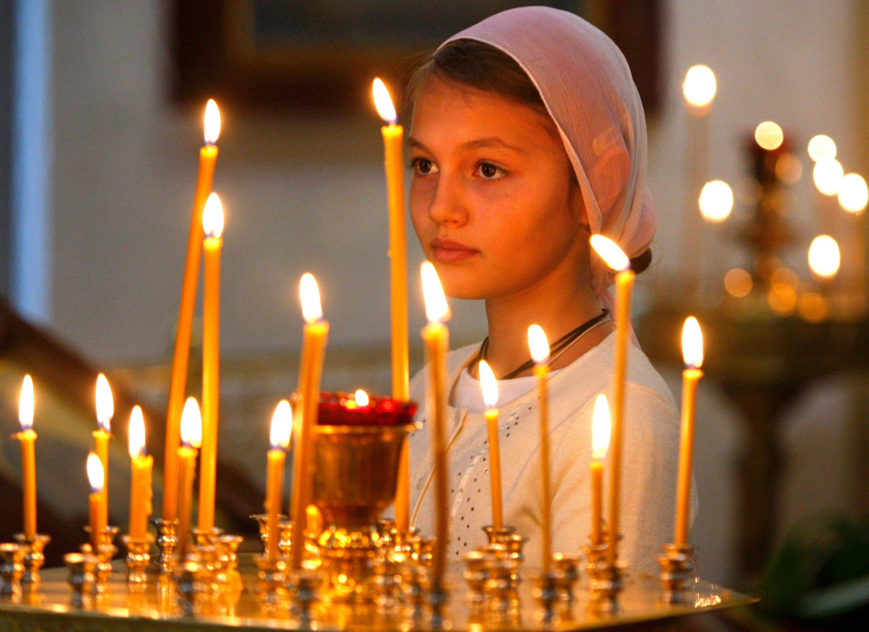 A girl attends an Orthodox service at St. Catherine in remembrance of the victims of the Sept. 11, 2001 terror attacks, Moscow, Sunday, Sept. 11, 2011. Sunday marks the tenth anniversary of the attacks of September 11, 2001.