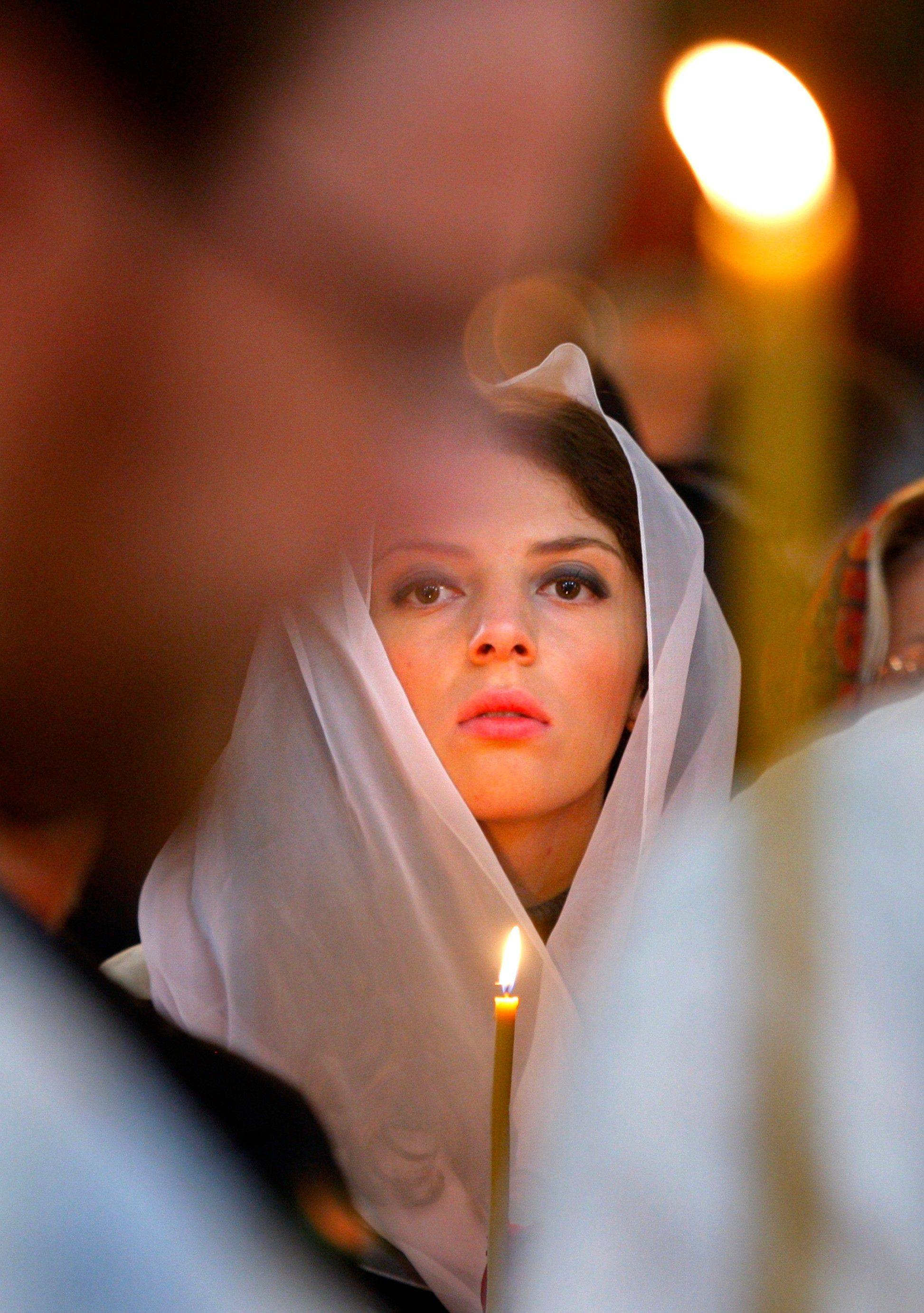 A woman holds a candle during an Orthodox service at St. Catherine in remembrance of the victims of the Sept. 11, 2001 terror attacks, Moscow, Sunday, Sept. 11, 2011. Sunday marks the tenth anniversary of the attacks of September 11, 2001.