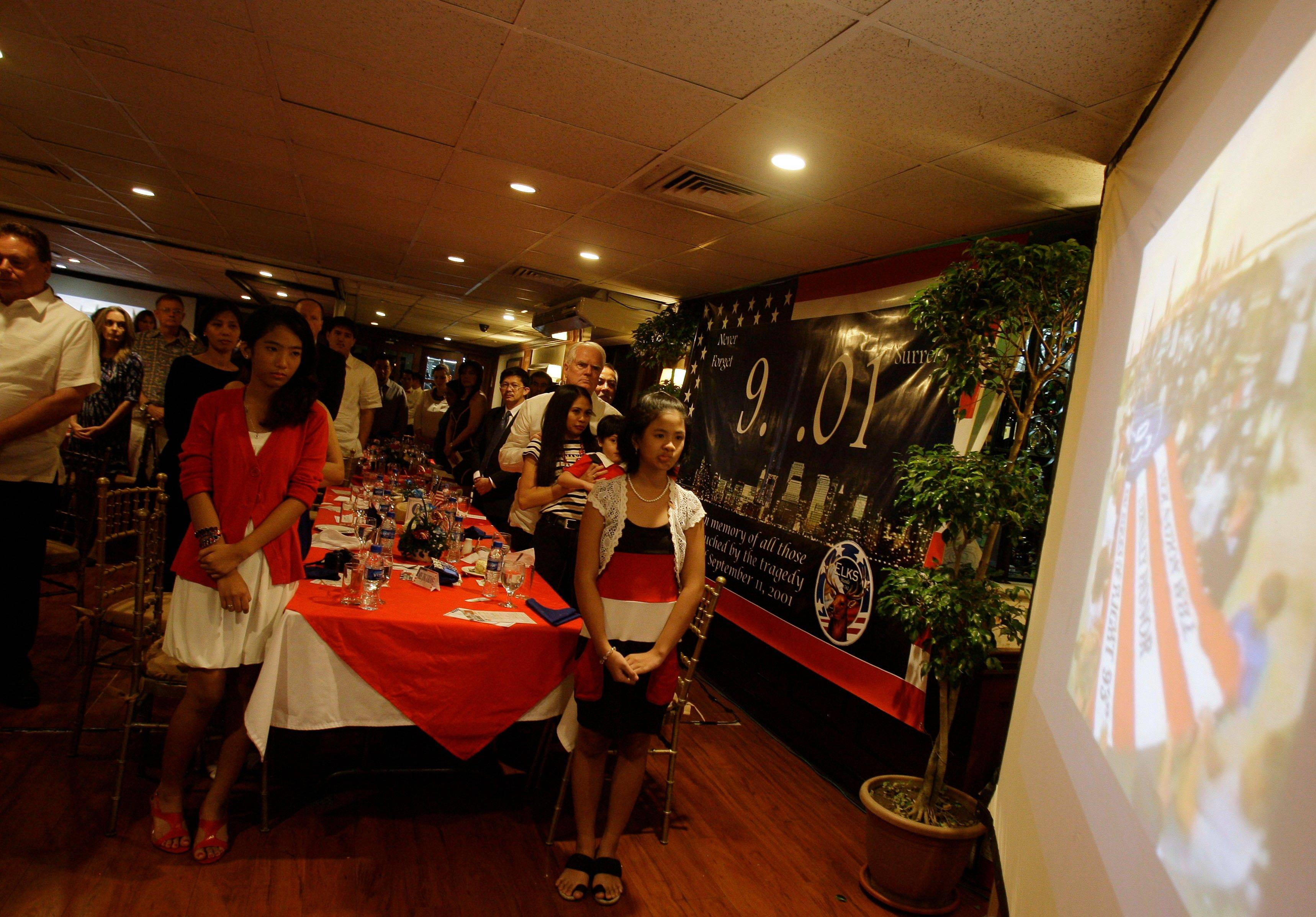 Guests stand during a gathering to mark the 10th anniversary of the Sept. 11 terror attacks in suburban Makati, south of Manila, Philippines Sunday Sept. 11, 2011. The group offered prayers for victims and viewed an exhibit about the attacks.