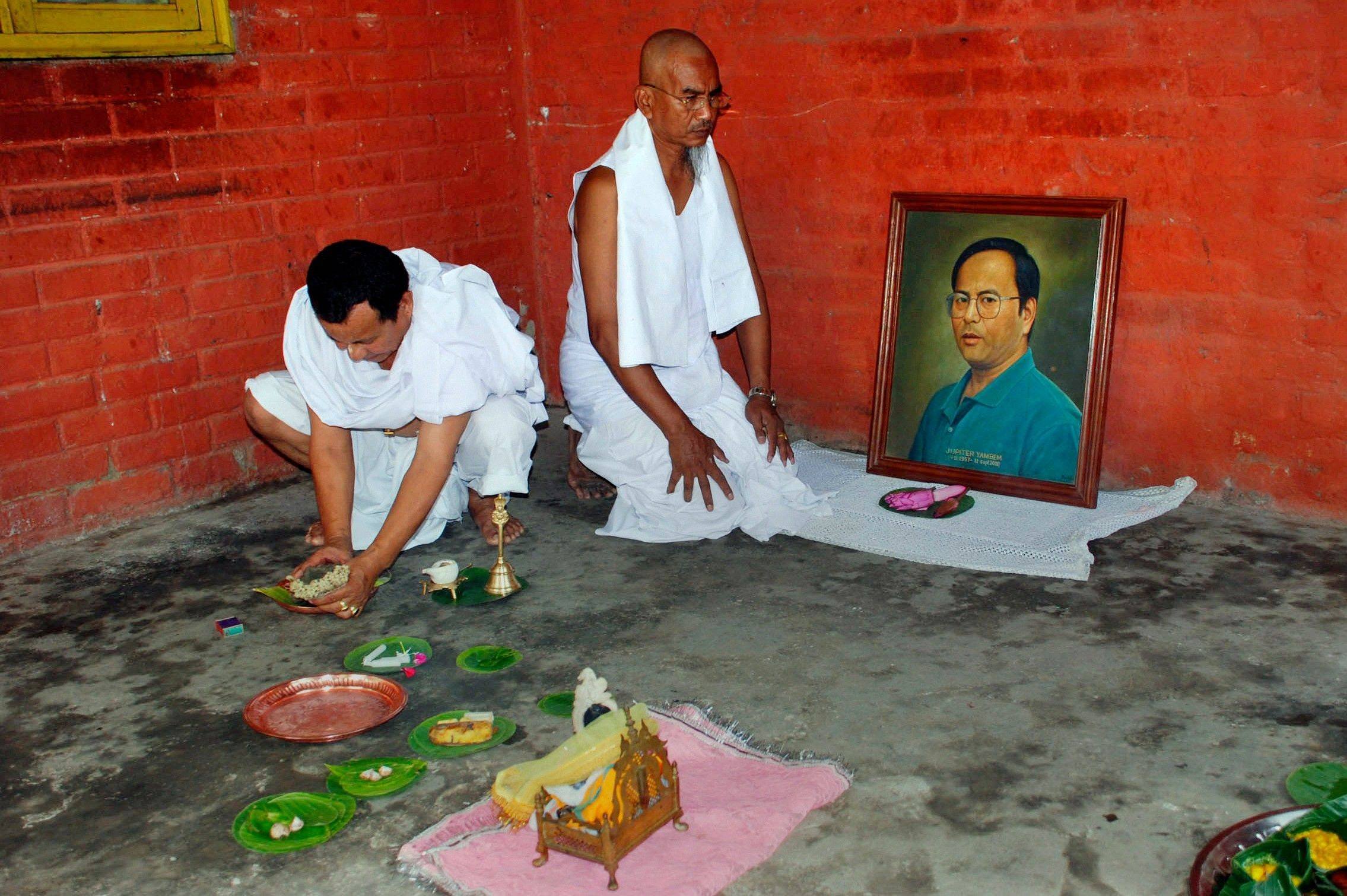 Family members offer prayers during a memorial service for Jupiter Yambem, shown in the photo, at his ancestral home in Imphal, in northeastern Indian state of Manipur, Sunday, Sept. 11, 2011. Around 100 family members and close friends gathered early Sunday to pay their respect to Yamben, who was killed in the attack on the World Trade Center. He was a banquet manager in Windows on the World restaurant atop one of the towers.