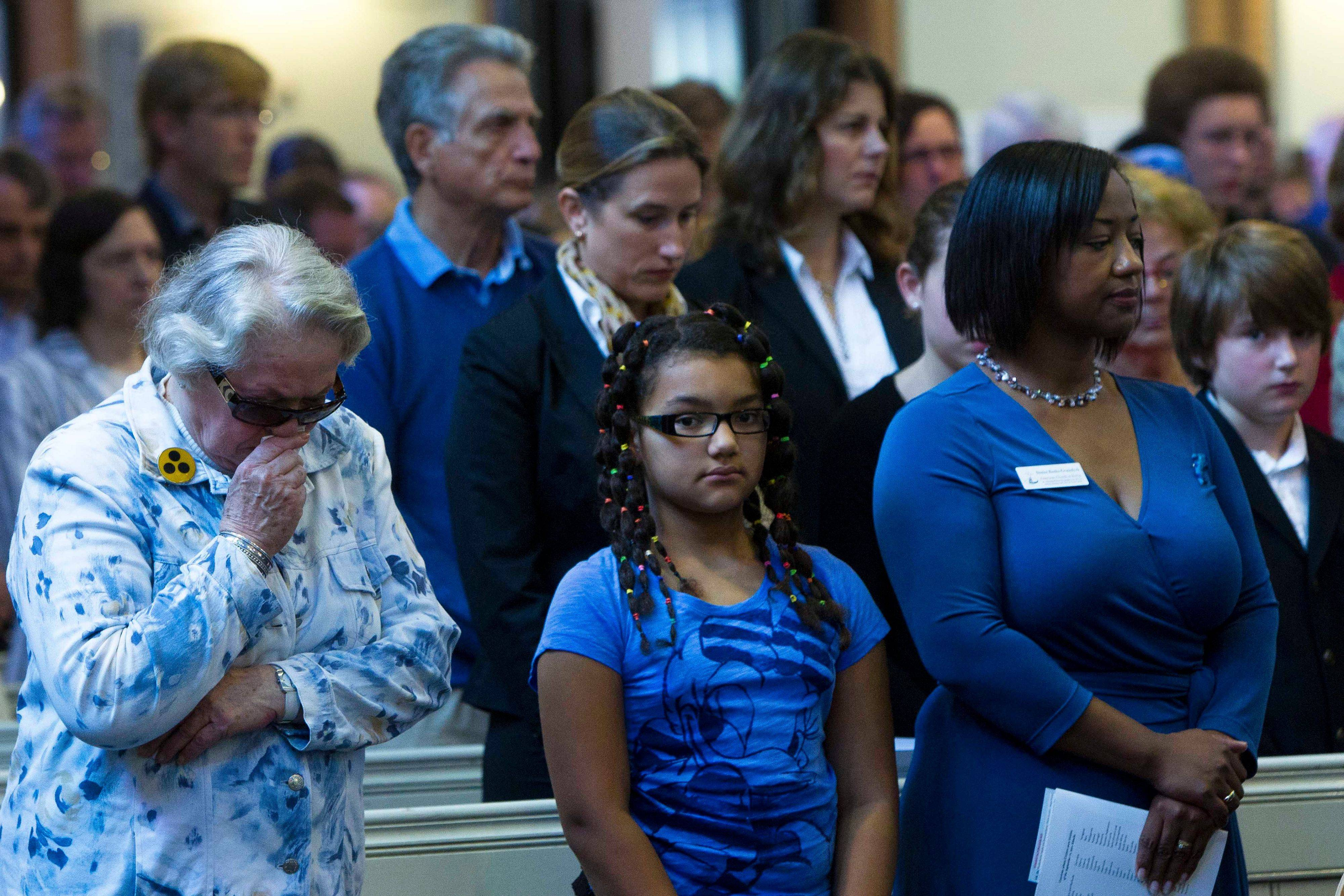People react during a minute of silence during a memorial service to commemorate the 10th anniversary of the Sept. 11 terror attacks at the American Church in Berlin, Sunday, Sept. 11, 2011.