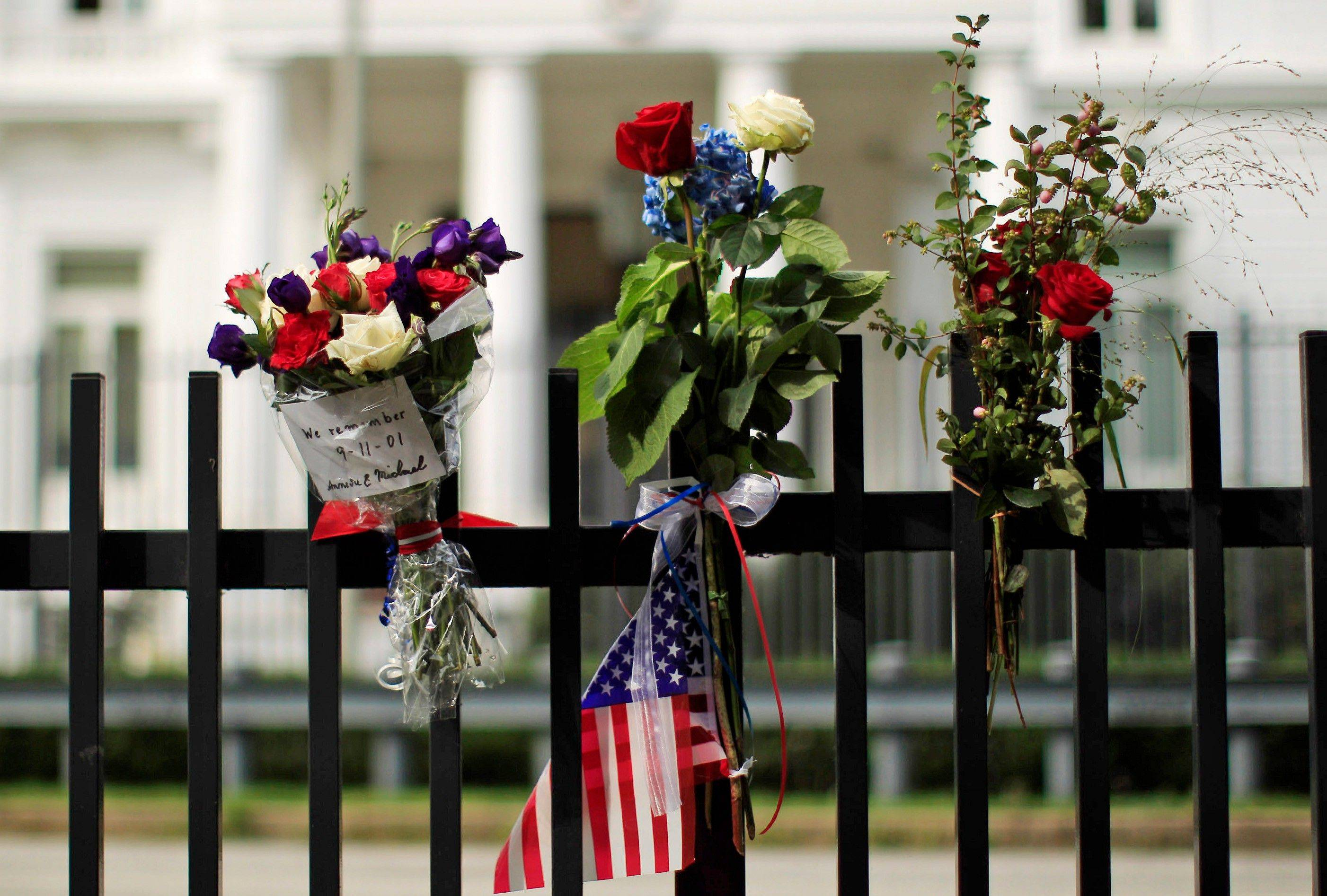 Flowers and a U.S flag are seen on the fence surrounding the U.S. Consulate as a commemoration to victims of the Sept. 11, 2001 attacks in Hamburg, northern Germany, Sunday Sept. 11, 2011.