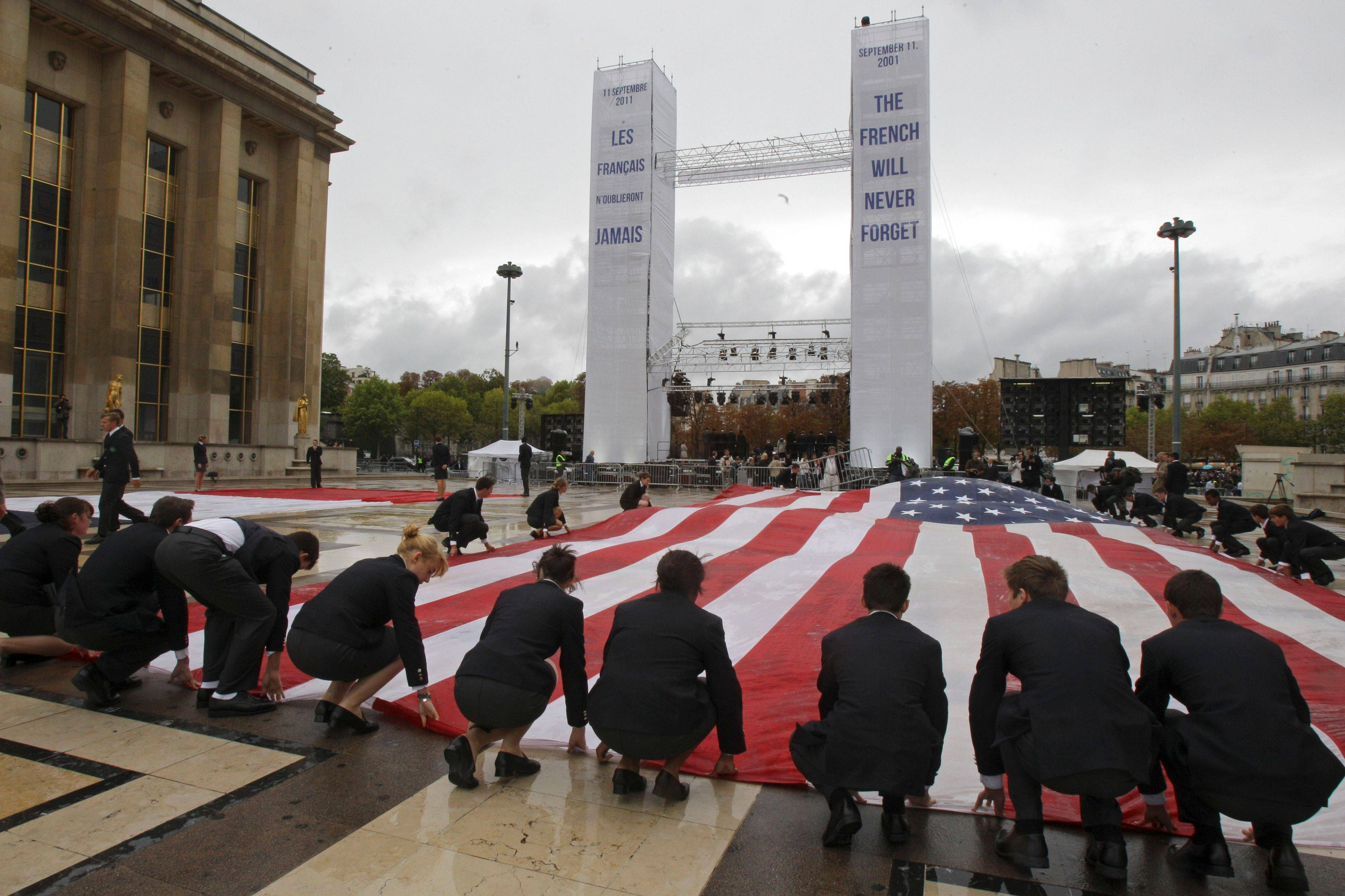 An American flag is unfurled during a commemoration to mark the 10th anniversary of the Sept. 11 attacks on the United States, at the Trocadero plaza , near the Eiffel tower in Paris, Sunday, Sept. 11, 2011.
