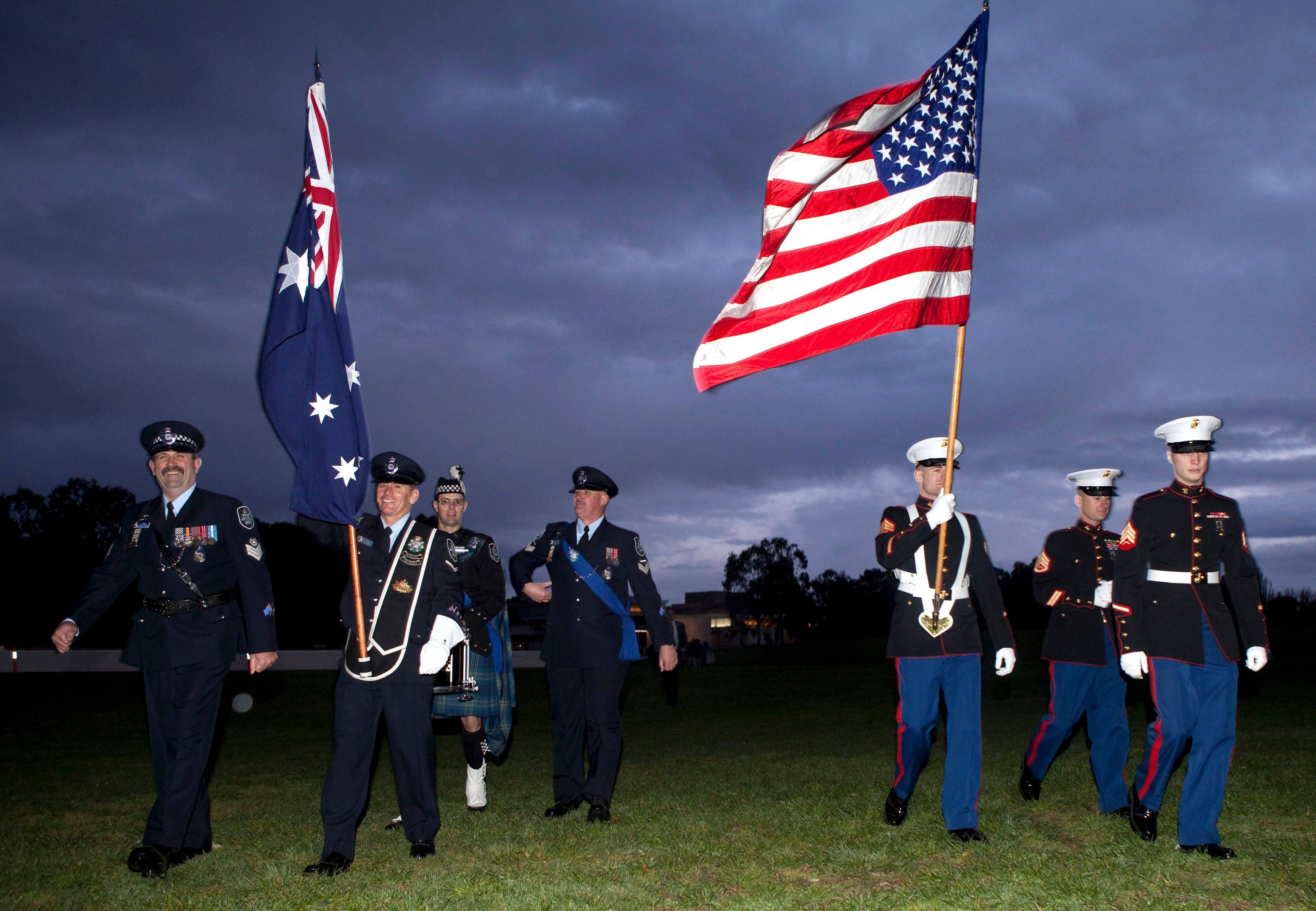 The Australian and American flags are withdrawn after a remembrance service marking the 10th anniversary of the Sept. 11 attacks in the US, in Canberra, Australia, Sunday, Sept. 11, 2011.