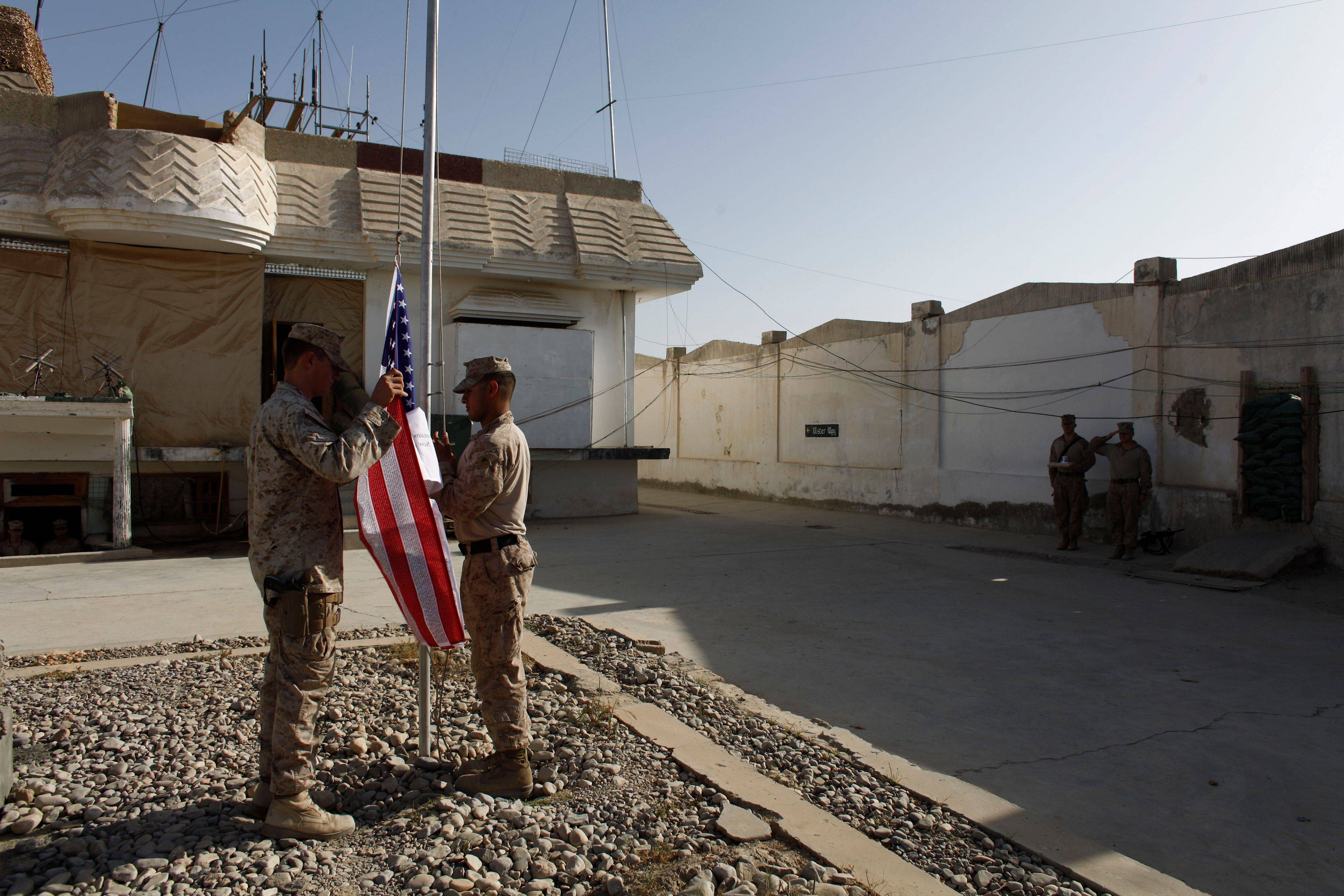 U.S. Marines raise a memorial American flag imprinted with the names of the Sept. 11, 2001 attack victims, at Forward Operating Base Jackson, in Sangin, Helmand province, Sunday Sept. 11, 2011. Ten years have passed since the deadly suicide attacks of Sept. 11, 2001 led the United States to wage war in Afghanistan.