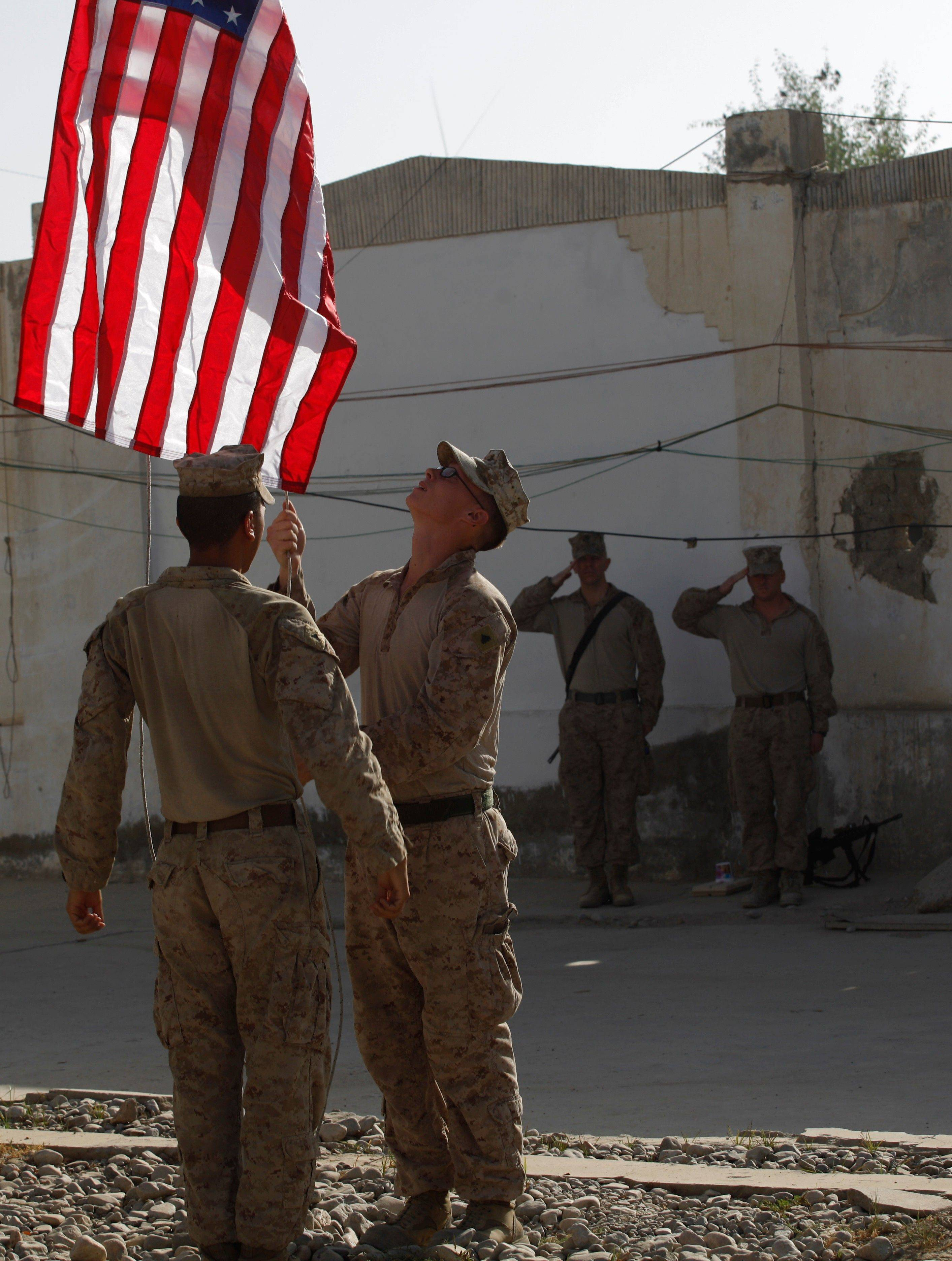 U.S. Marines raise the American flag in the morning at Forward Operating Base Jackson, in Sangin, Helmand province, Sunday Sept. 11, 2011. Ten years have passed since the deadly suicide attacks of Sept. 11, 2001 led the United States to wage war in Afghanistan.