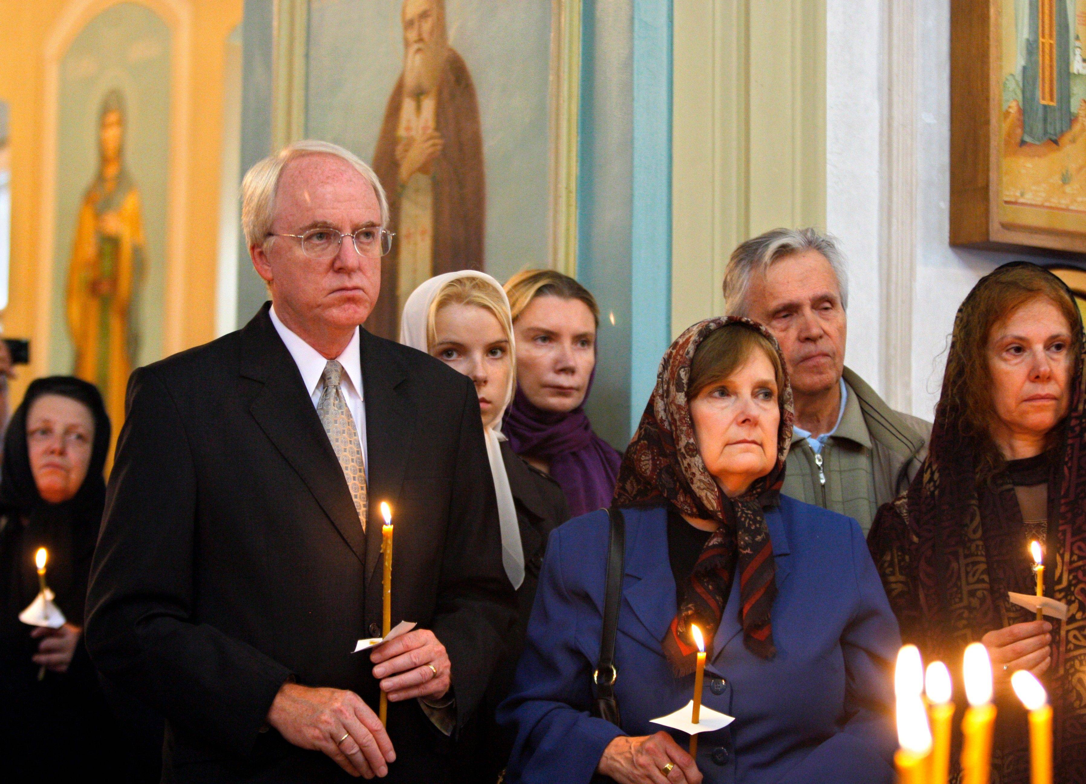 The US Ambassador to Russia John Beyrle, foreground left, holds a candle at the Church of St. Catherine in remembrance of the Sept. 11, 2001 victims in Moscow on Sunday, Sept. 11, 2011. Sunday marks the tenth anniversary of the attacks of September 11, 2001. The ambassador participated in events to commemorate all victims of the September 11 terror attacks in US.