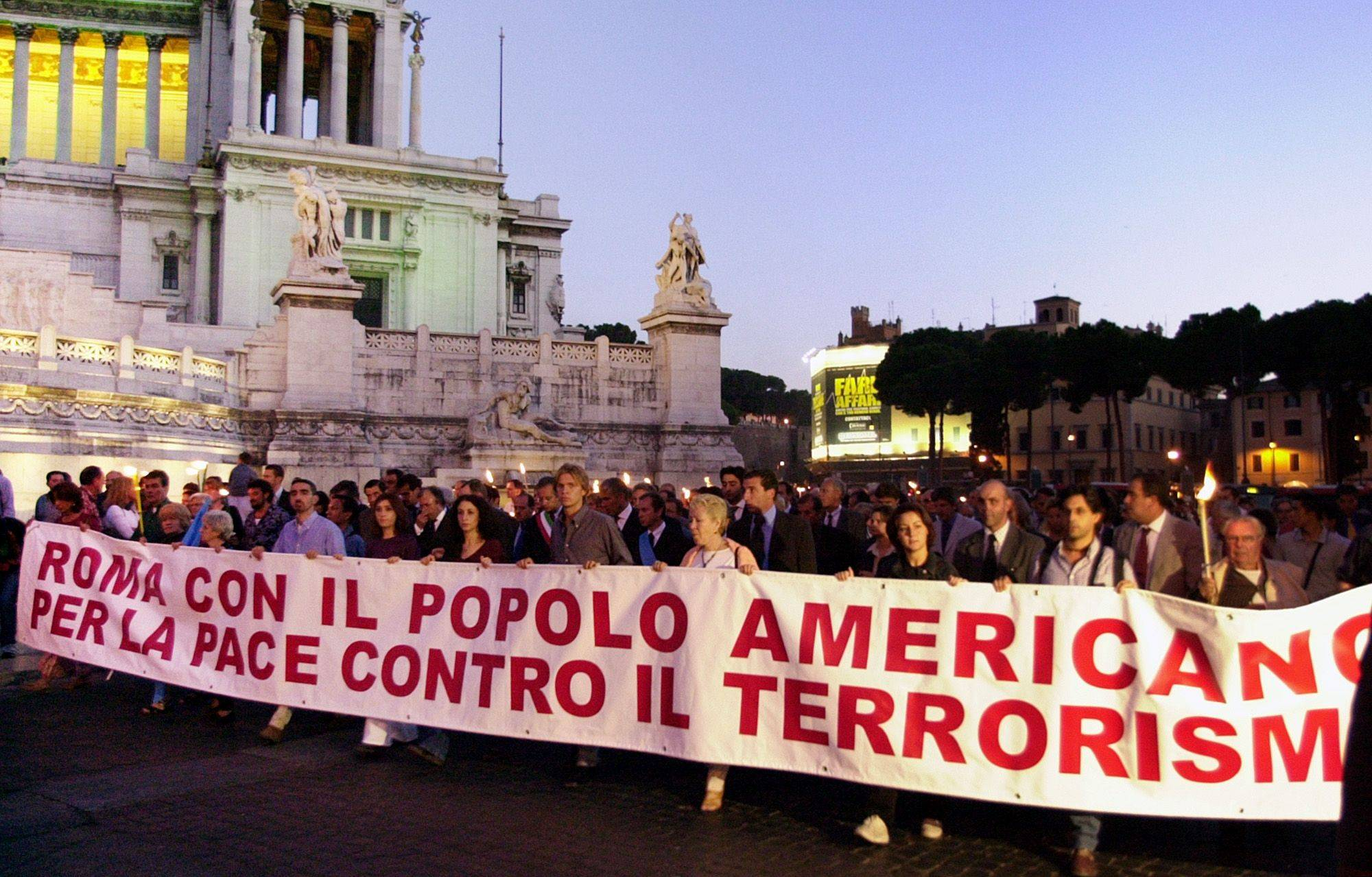 "Italian demonstrators carry a banner saying: ""Rome is with the American People, for Peace against Terrorism"" the day after the Sept. 11 attacks in the U.S."