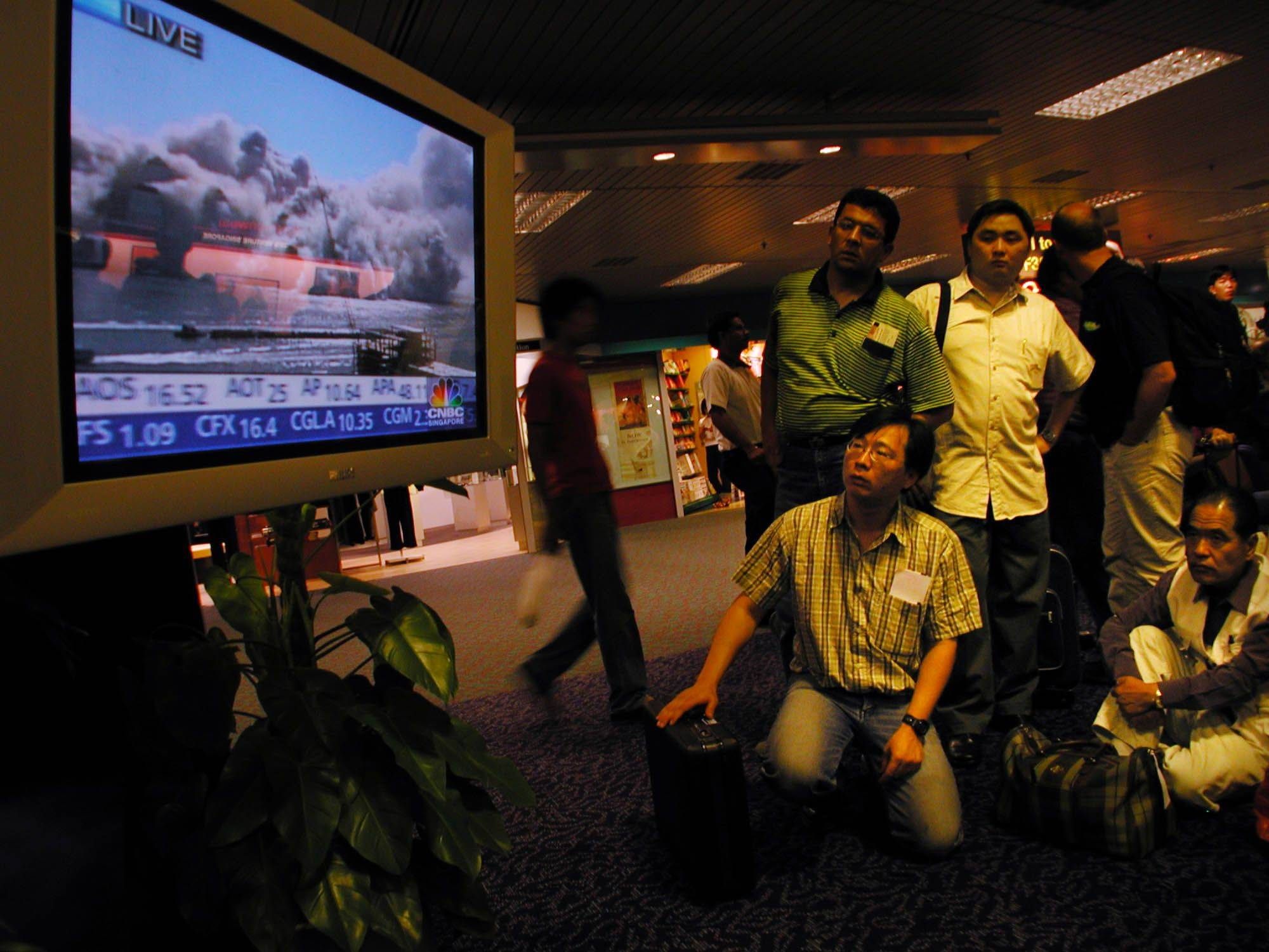 Travelers at Singapore's Changi International Airport stop to watch live pictures of smoke billowing over lower Manhattan after the terrorist attacks on the World Trade Center.