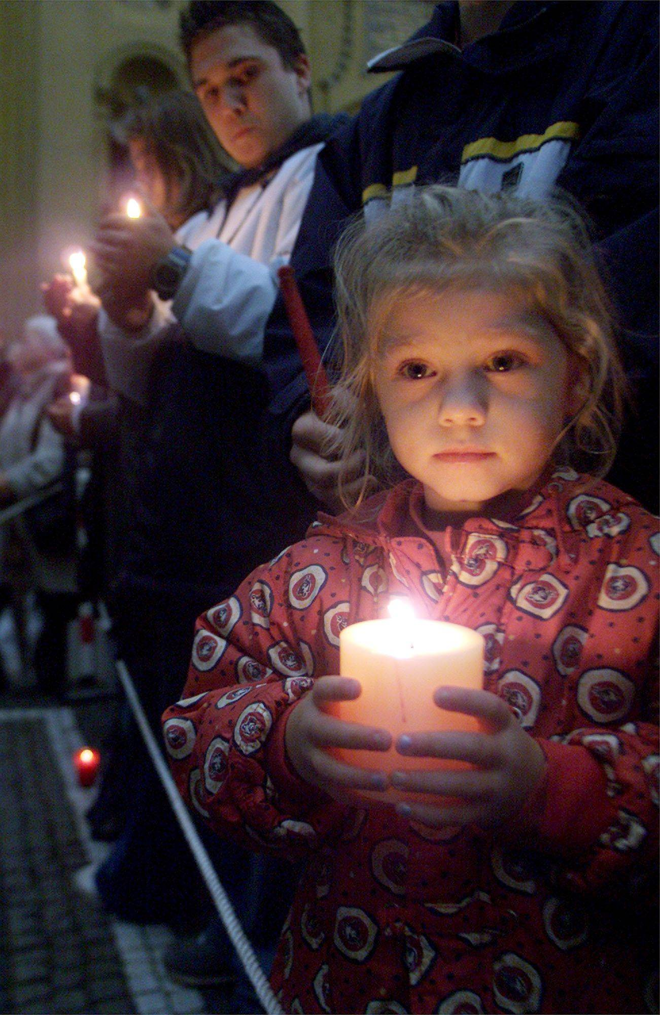 A little girl holds a candle while standing with hundreds of mourners in downtown Munich, Germany, on Sept. 12, 2001, during a ceremony for the victims of the terrorist attacks in the United States.