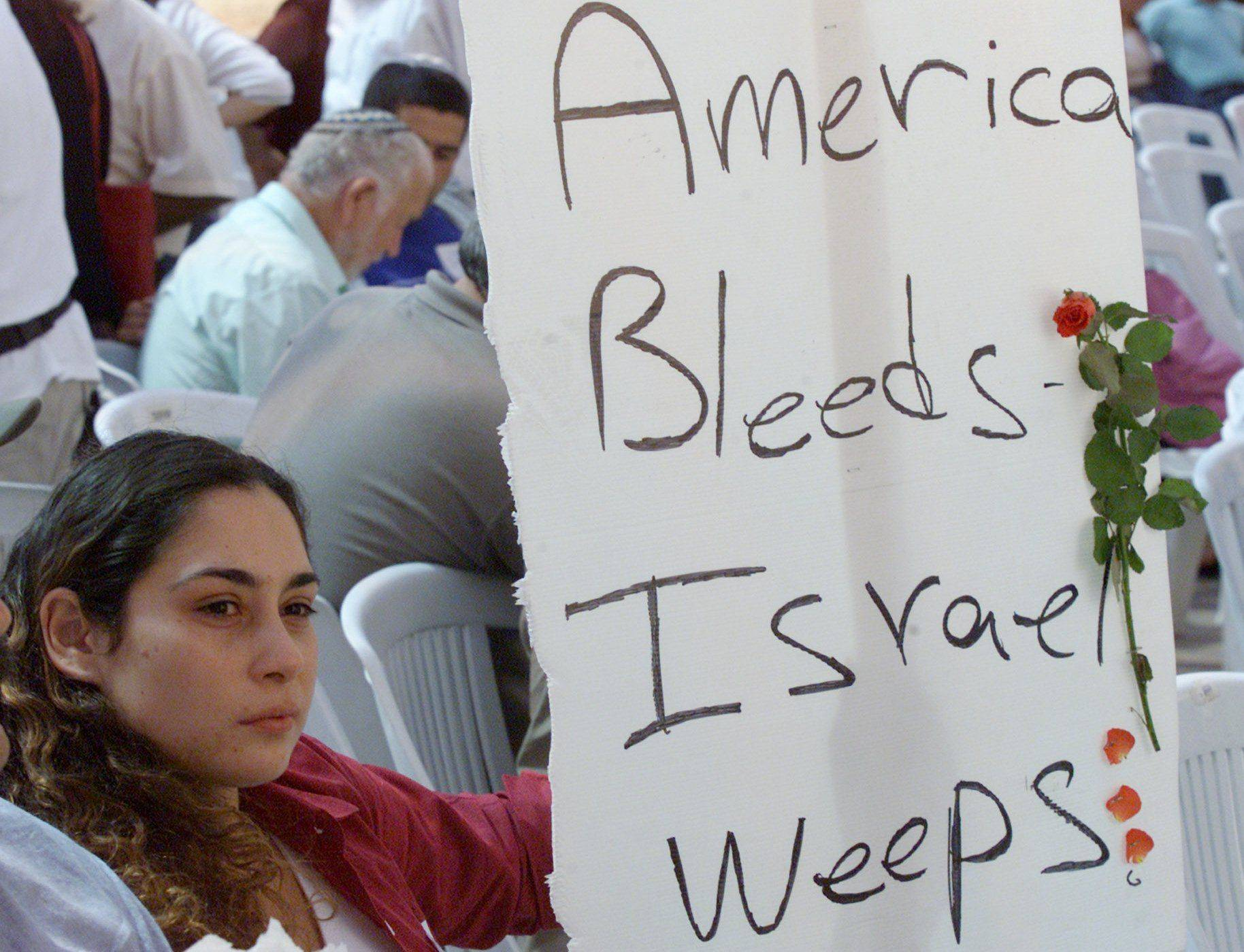 Israeli Moran Cohen holds a sign in support of the victims of Sept. 11 attacks in the United States during a ceremony in Jerusalem on Sept. 12, 2001.