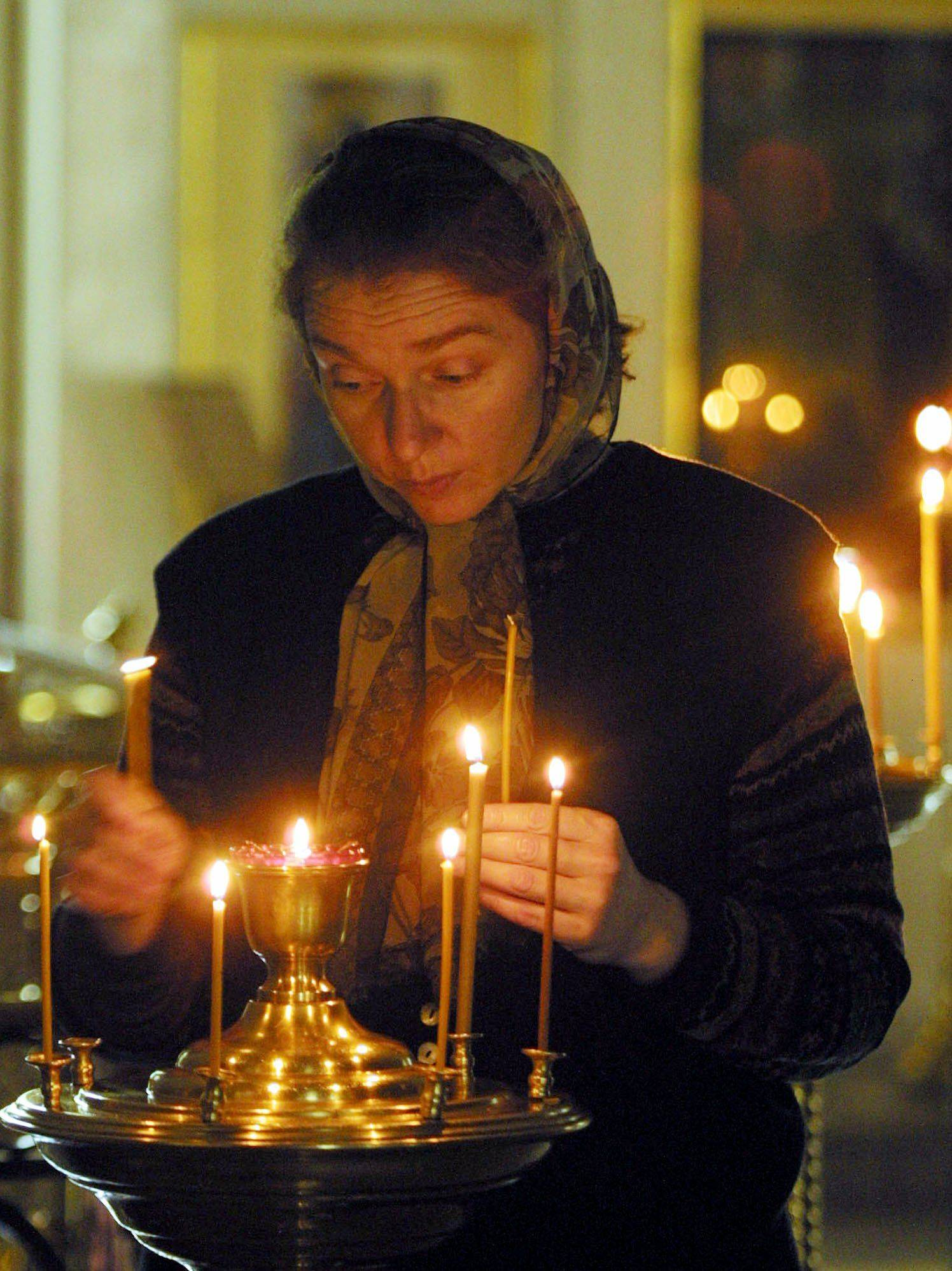 A Russian woman lights candles mourning the victims of the terrorist attacks in the United States during a special service at St. Nicholas Cathedral in Moscow on Sept. 14, 2001.