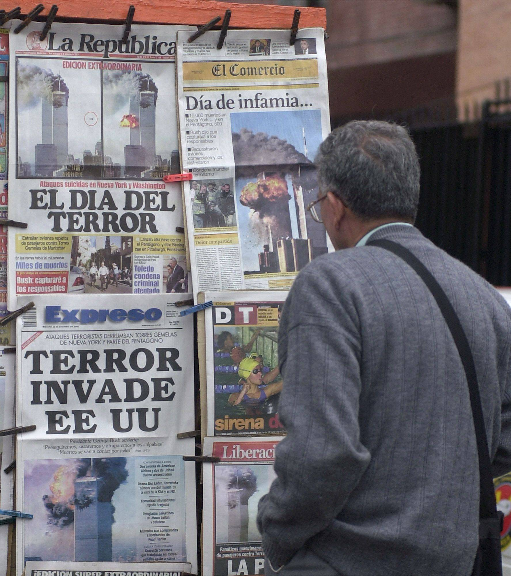 "A man in Lima, Peru, reads the front pages of local newspapers where headlines read: ""Day of terror,"" ""Day of infamy,"" and ""Terror invades the United States"" on Sept. 12, 2001."
