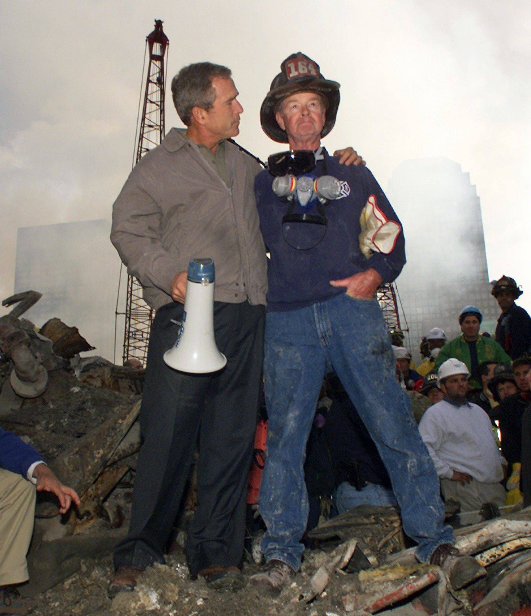 President George W. Bush puts his arm around firefighter Bob Beckwith while standing in front of the World Trade Center in New York during a tour of the devastation on Sept. 14, 2001.