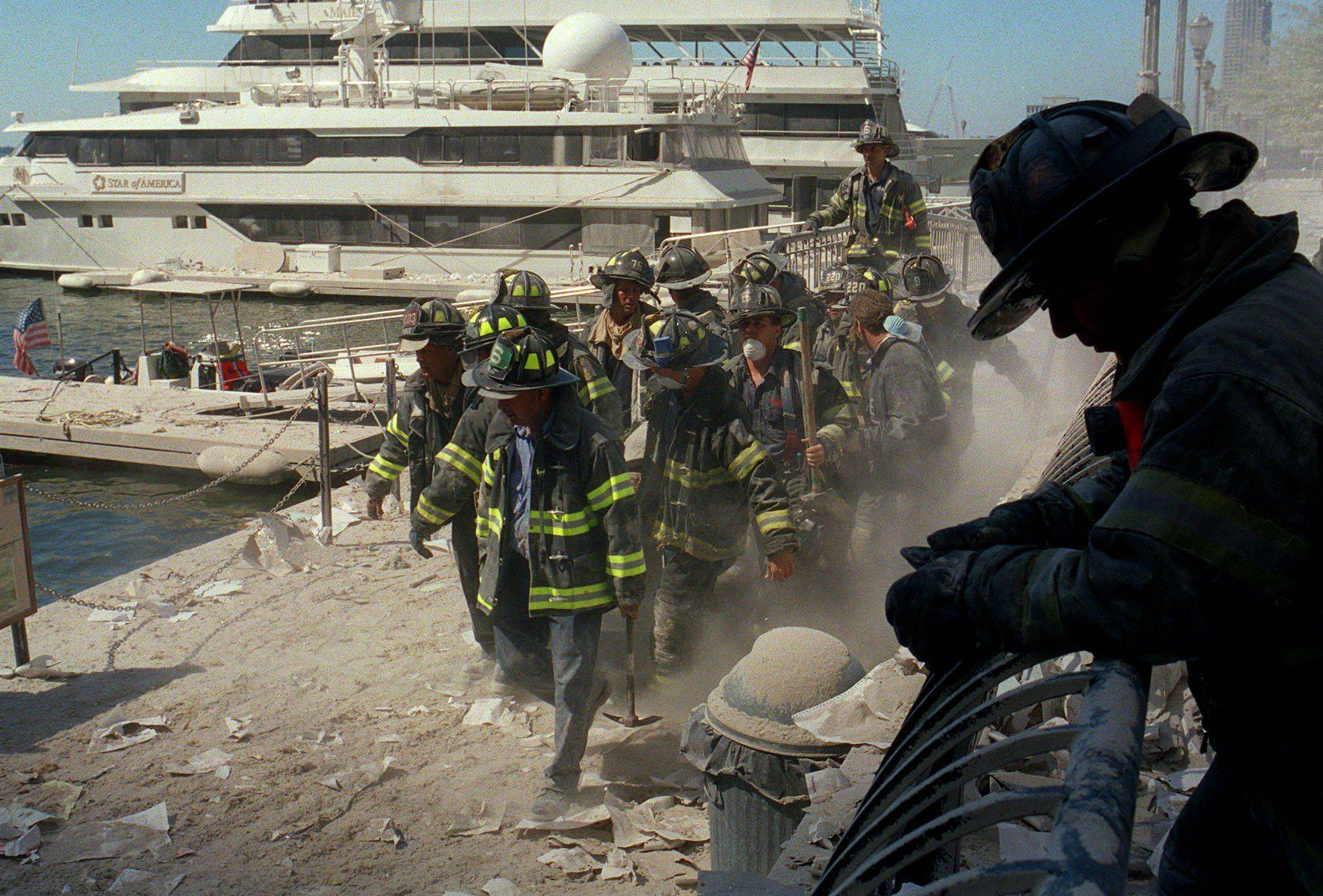 Firefighters carry an injured fireman from the World Trade Center area in New York after the buildings collapsed Sept. 11, 2001.