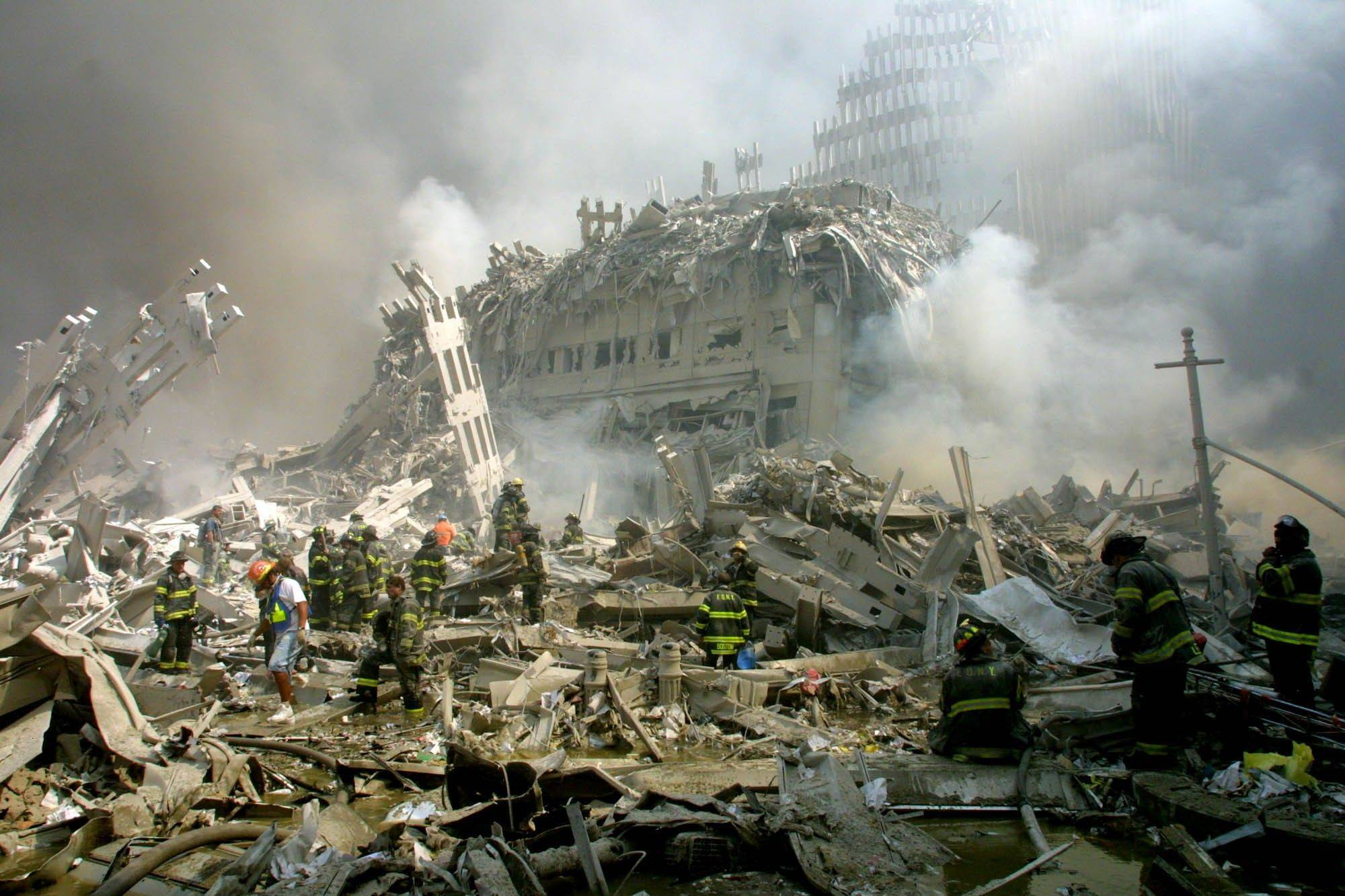 Firefighters walk through the rubble of the collapsed World Trade Center buildings after terrorists crashed two airliners into the towers.