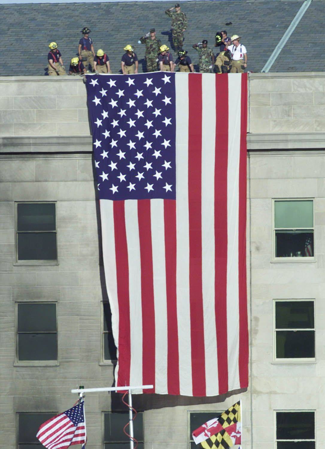 Firefighters unfurl an American flag from the roof of the Pentagon on Sept. 12, 2001, as President George W. Bush visits the area.