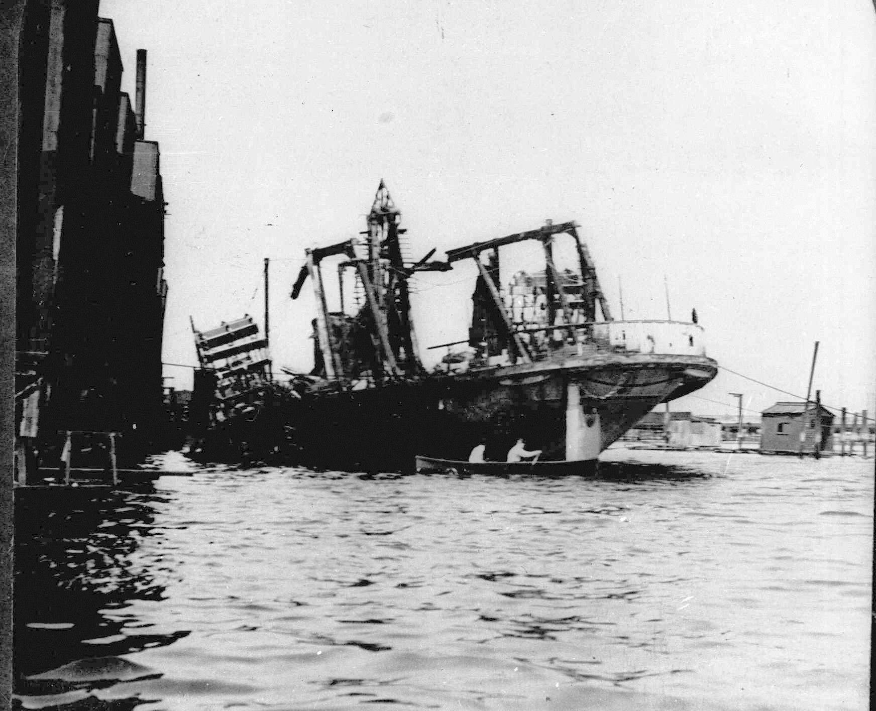 The excursion boat General Slocum lies beached off Hell Gate in New York City's East River, following a fire and resulting panic. The disaster cost the lives of 1,030 mostly German immigrants on June 15, 1904.