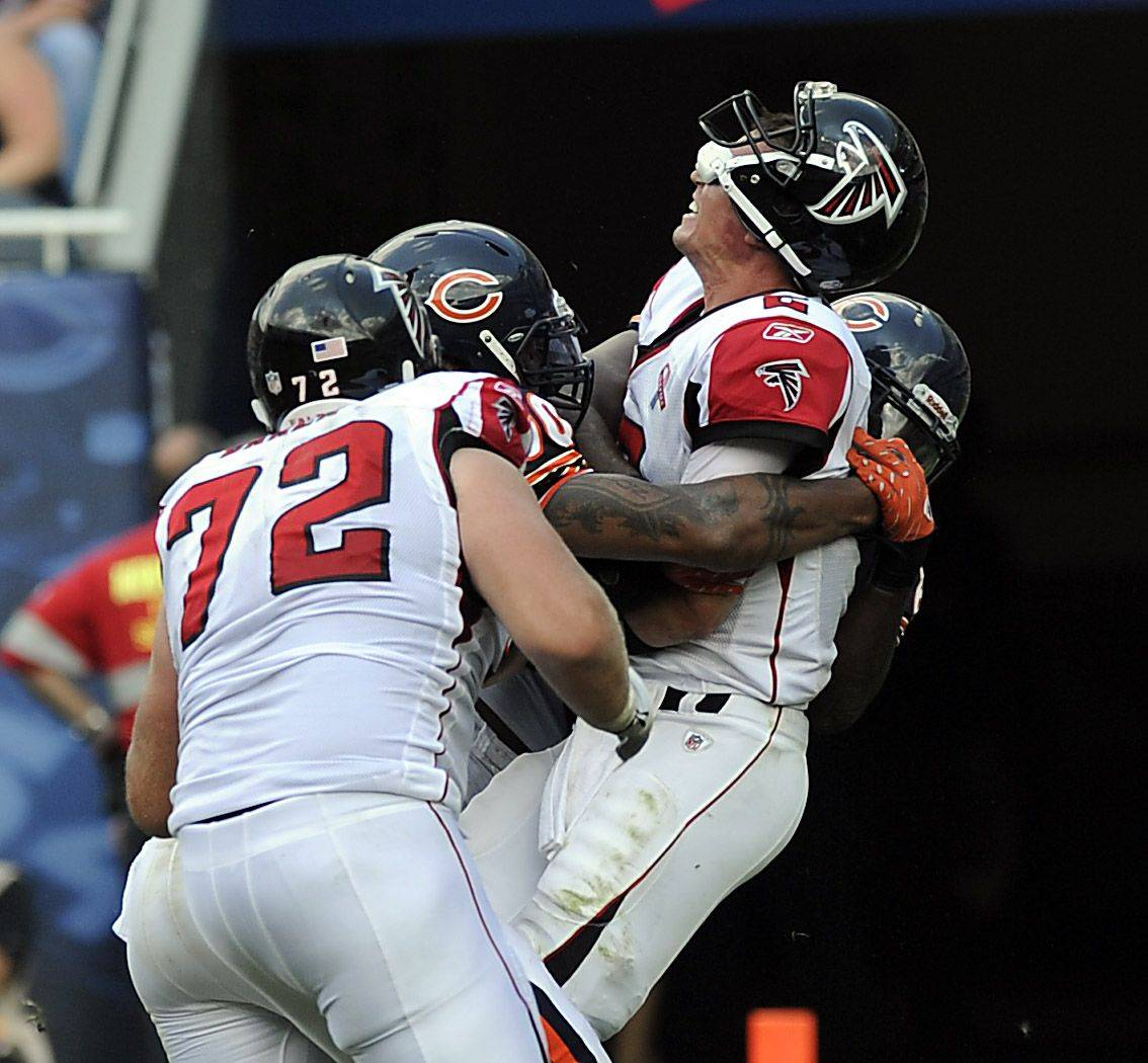 Julius Peppers and Henry Melton pop Falcons quarterback Matt Ryan in the fourth quarter of the Bears' victory Sunday at Solider Field.