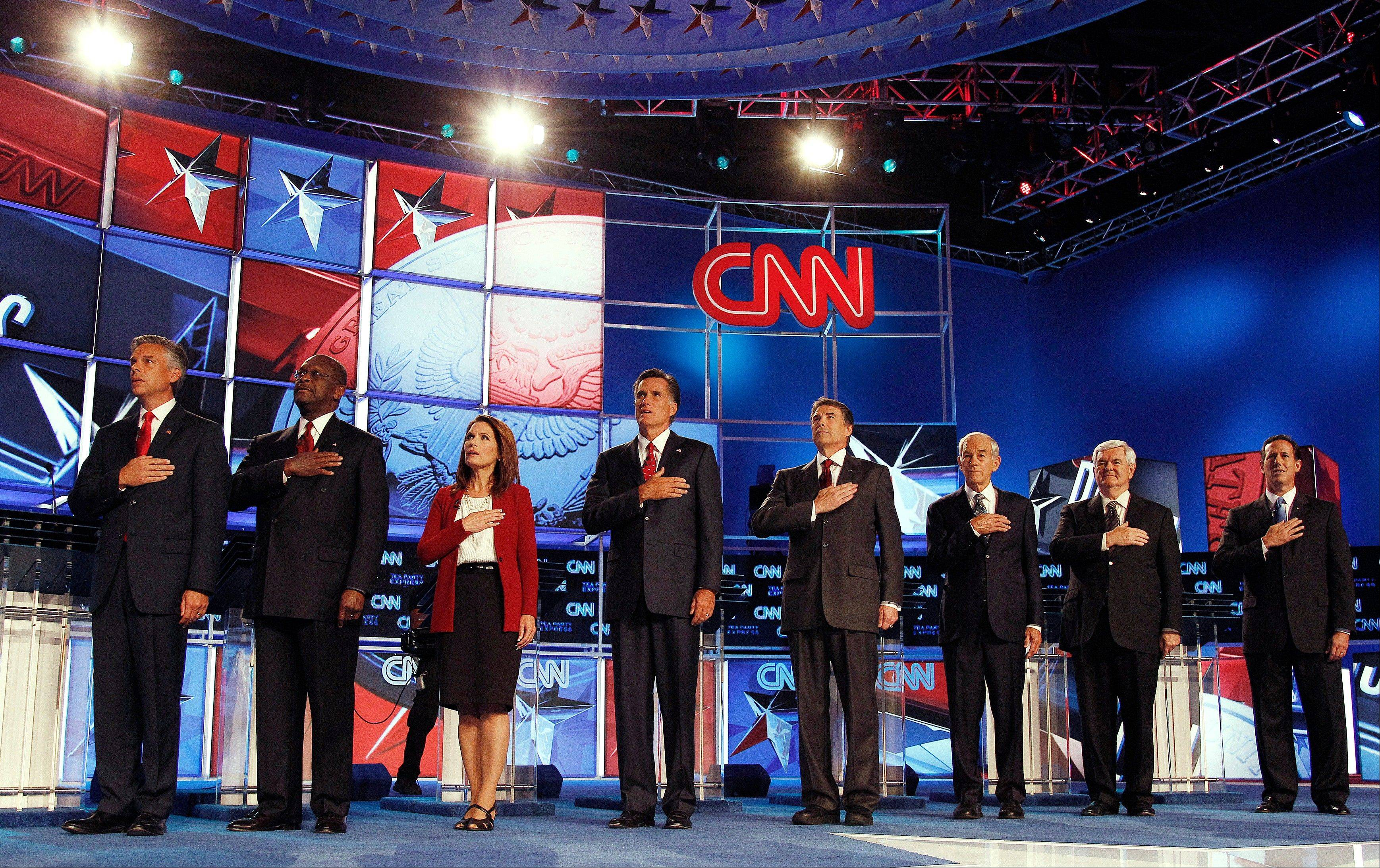 Republican presidential candidates, from left, Utah Gov. Jon Huntsman, businessman Herman Cain, Rep. Michele Bachmann, R-Minn., former Massachusetts Gov. Mitt Romney, Texas Gov. Rick Perry, Rep. Ron Paul, R-Texas, former House Speaker Newt Gingrich, and former Pennsylvania Sen. Rick Santorum, sing the national anthem before a Republican presidential debate Monday, Sept. 12, 2011, in Tampa, Fla.