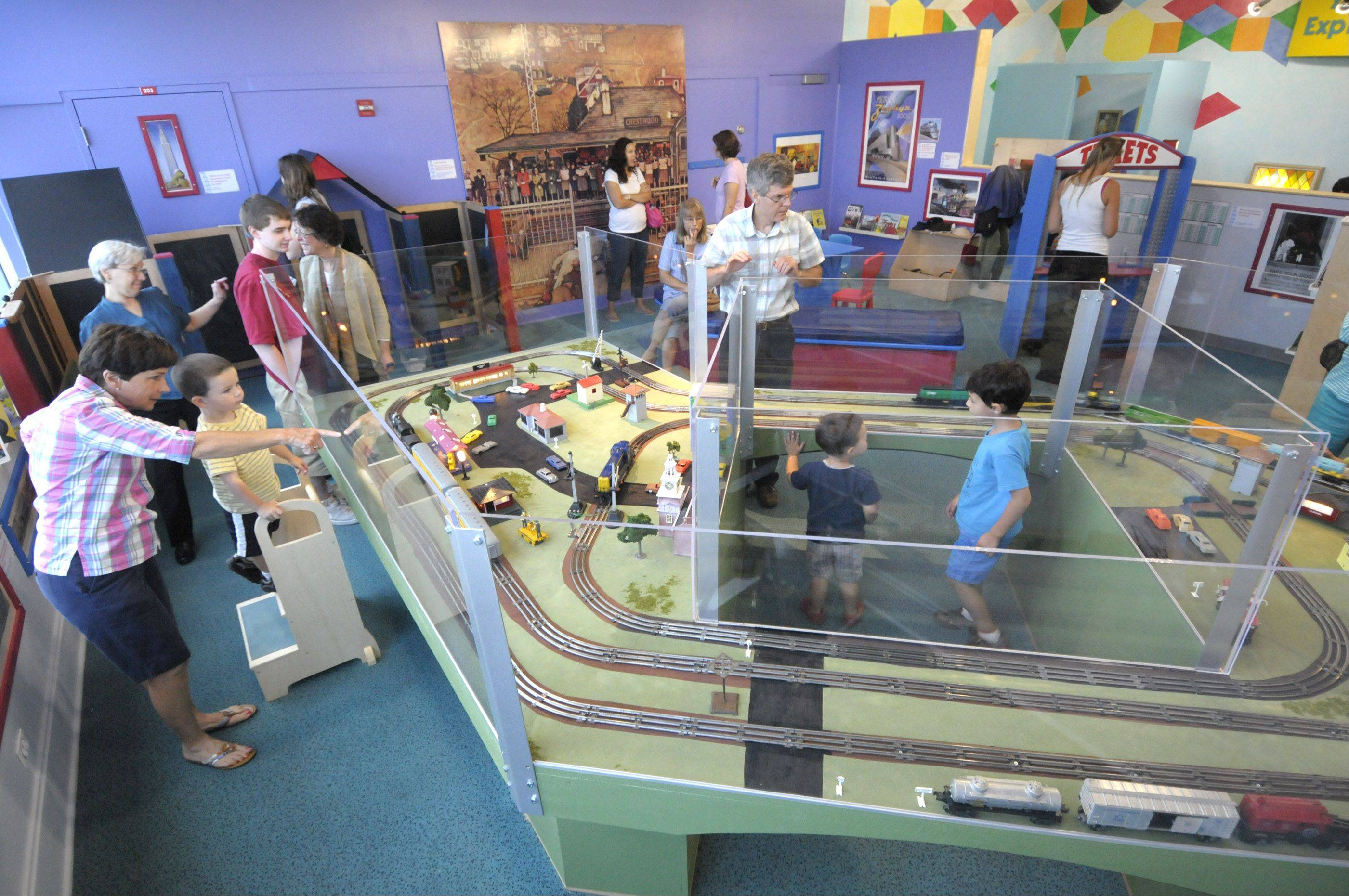 DuPage Children�s Museum�s new exhibit allows kids to pretend to be engineers, dispatchers and ticket agents. With the aid of a stepstool, left, Danny Flynn, and his grandmother Margie Flynn get a close-up view of the Lionel train layout.