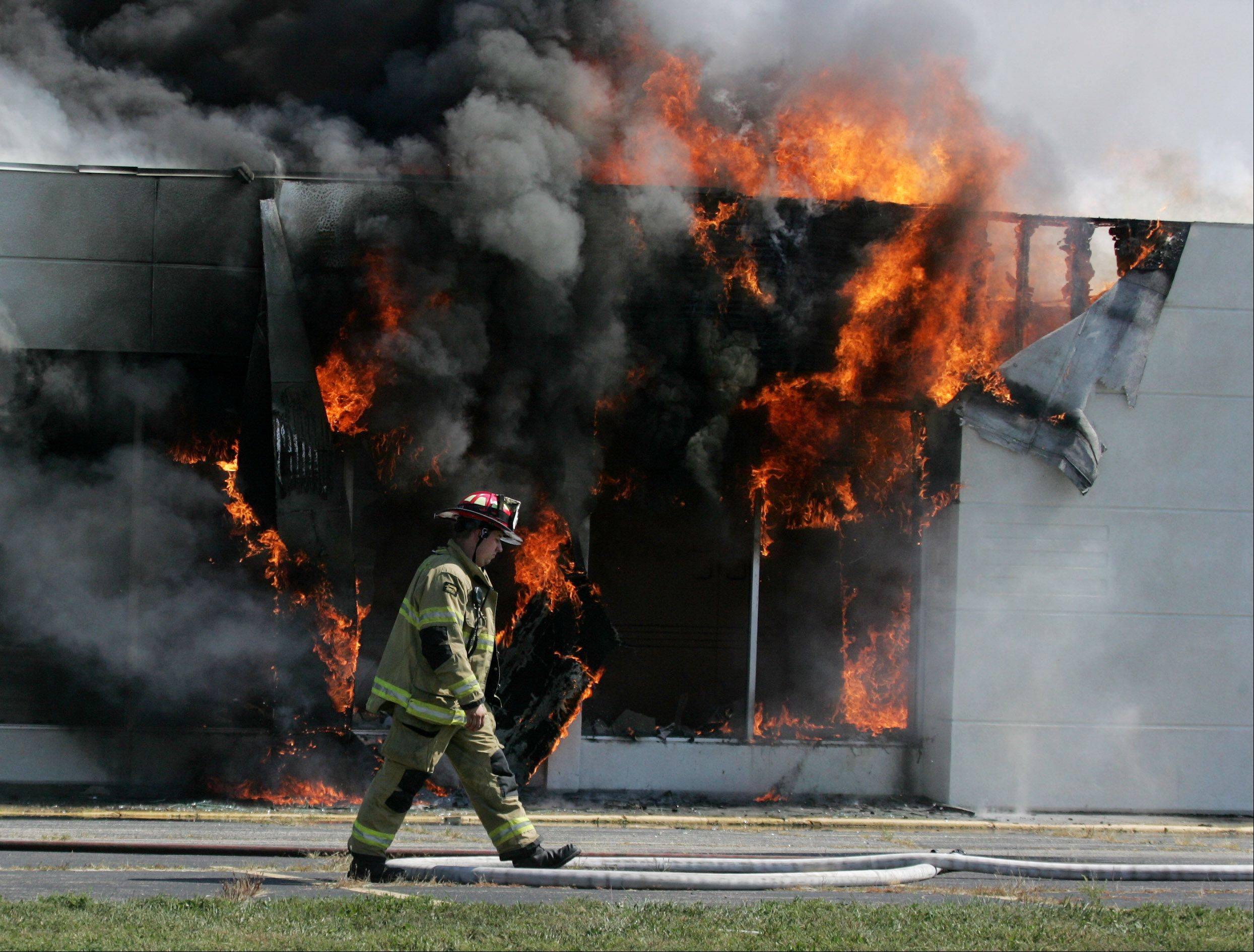 A firefighter walks past a burning blaze as firefighters from throughout Lake County were called to the scene of a fire at the Knights Inn hotel Monday in North Chicago. The fire broke out shortly before 10:30 a.m. at the vacant hotel on Green Bay Road.