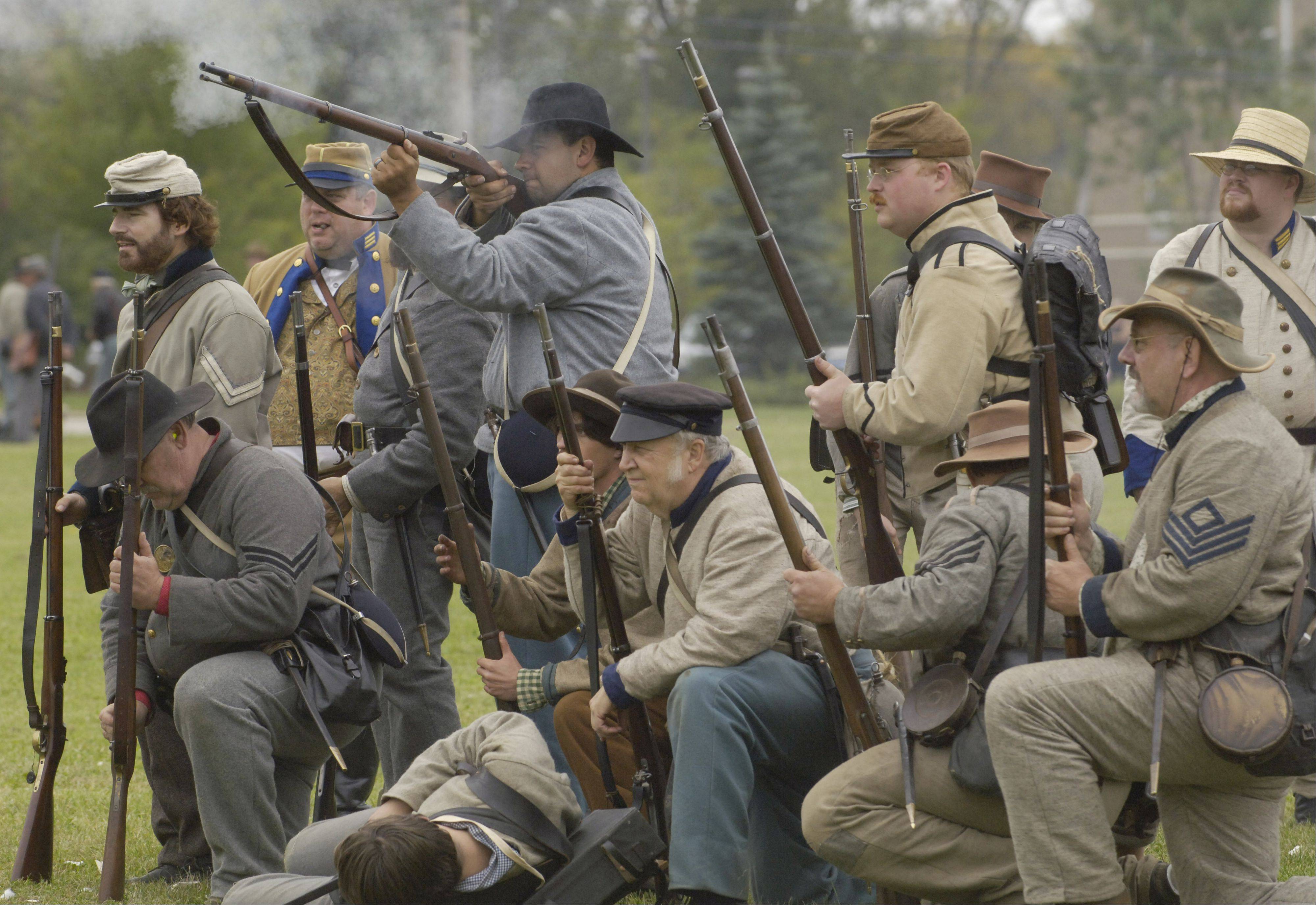 Confederate troops fire on Union positions in a battle re-enactment during Civil War Days at Lehmann Mansion in Lake Villa.