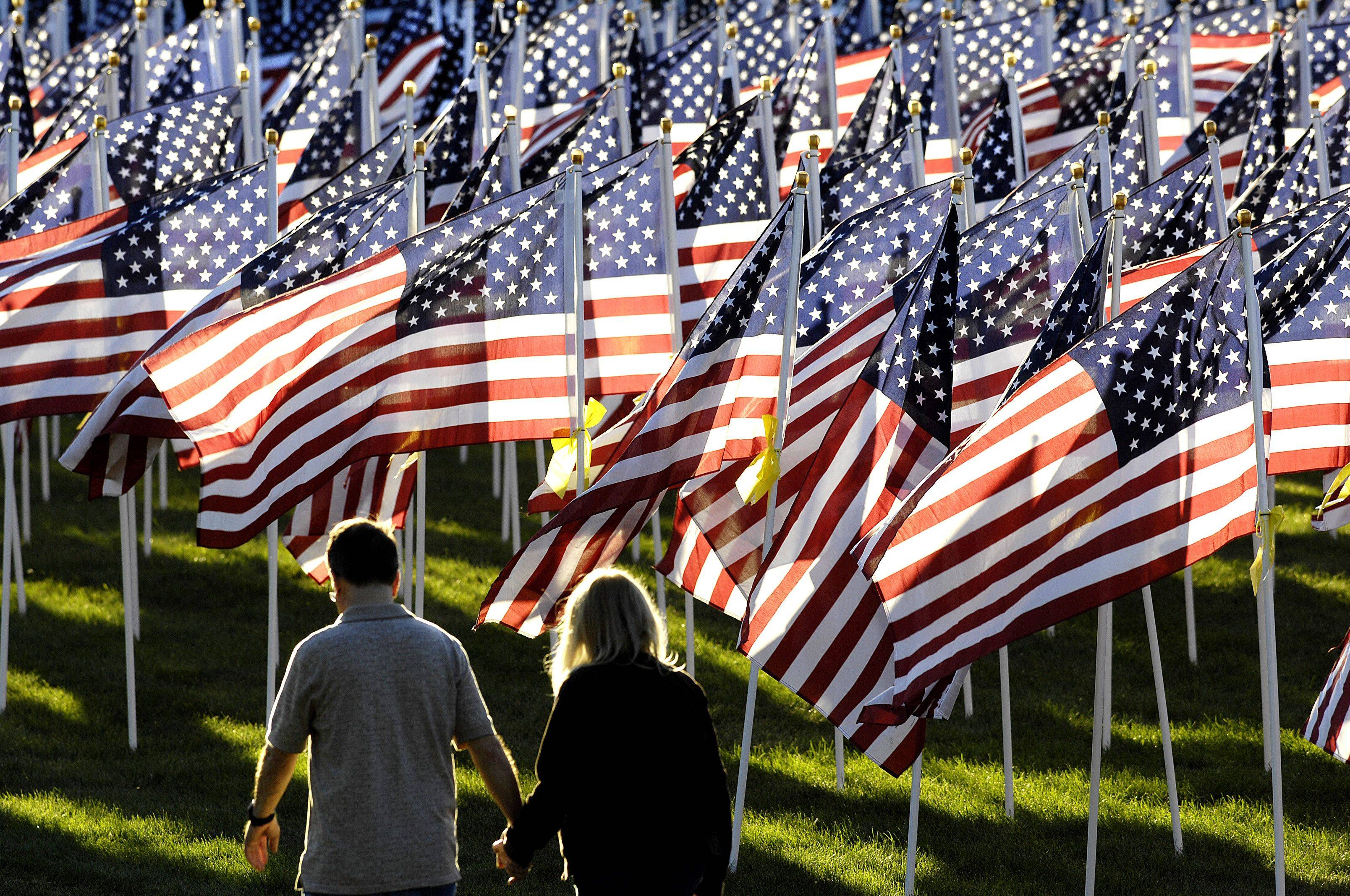 A couple hold hands in Carpenter park as they pass 2976 American Flags at a Healing Field event in Carpentersville Wednesday evening. There is one flag for every person who died on September 11, 2001 in the terrorist attacks. The Healing Field event will run through the weekend and include a candlelight vigil Saturday night. It is presented by the Patriot Committee of Dundee Township.