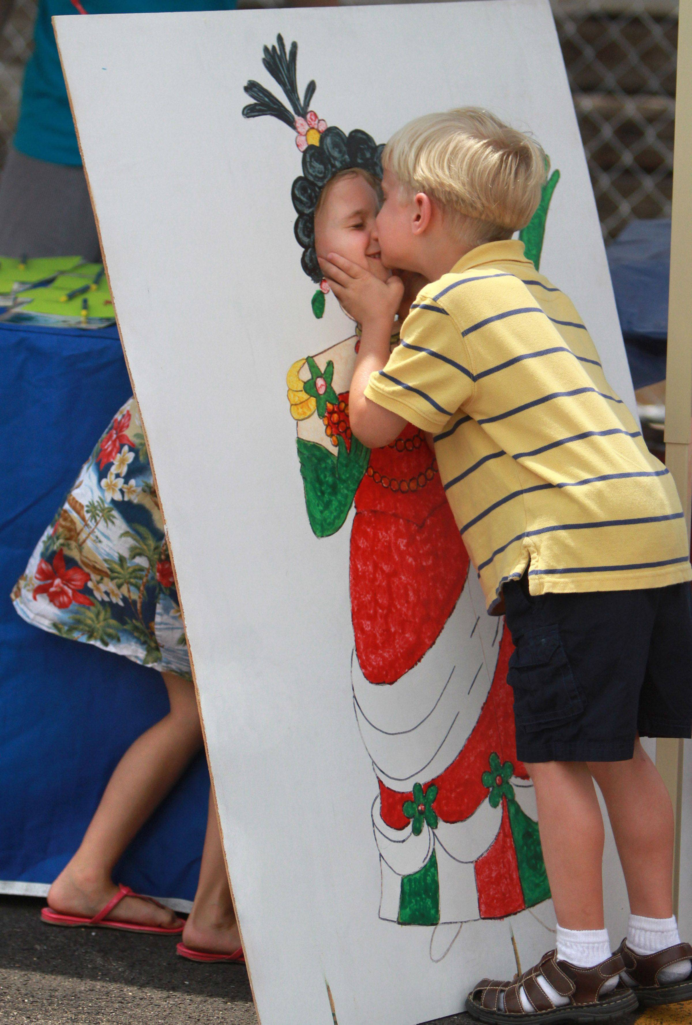 George Tarulis, 6, of Barrington Hills gives his twin sister a kiss through a photo face cutout at International Fest hosted by Barrington Breakfast Rotary Club near the train station in Barrington on Wednesday, June 6th. The one day festival included music, food, and games. July 2011