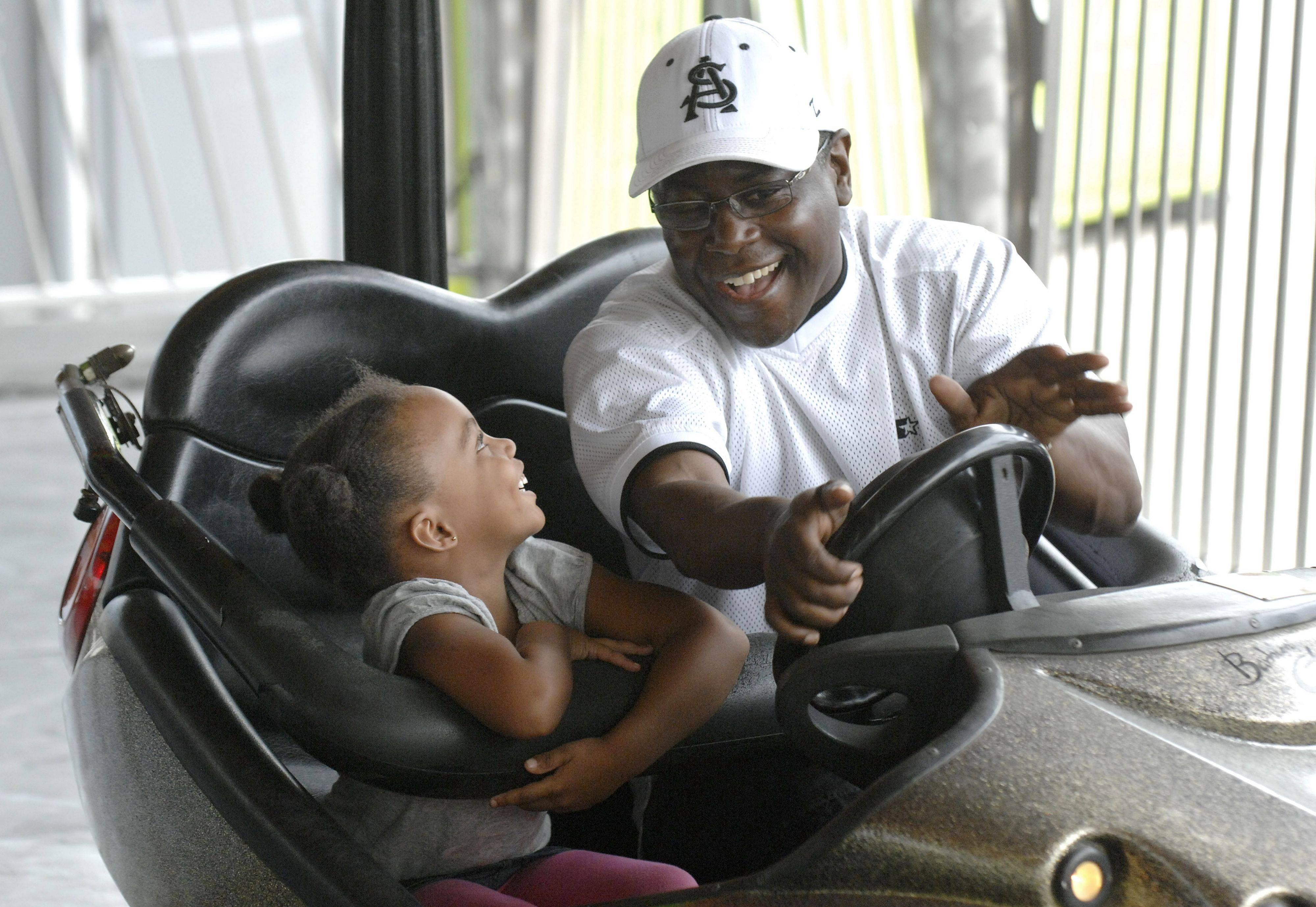 Bobby Moore of St. Charles and his granddaughter, Jordan Cotton, 4, of Berwyn, giggle after their first collision on the bumper cars at the carnival running over Labor Day weekend at Route 38 and Randall Rd in St. Charles. The carnival benefits the Literacy Volunteers Fox Valley and Fox Valley Troop Support.