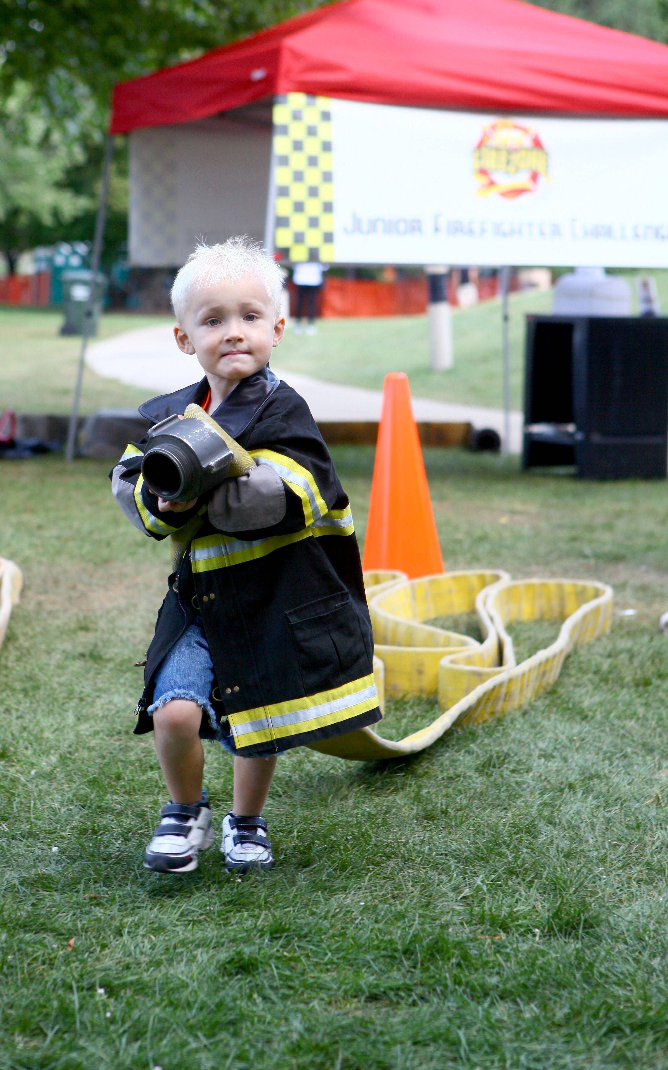 Ethan Frejd, 4, from Schaumburg carrys a fire hose across the Firezone course at September Fest Sunday afternoon in Schaumburg. Firefighters from all over the area work for Firezone to show kids and adults a little about the work a firefighter does.