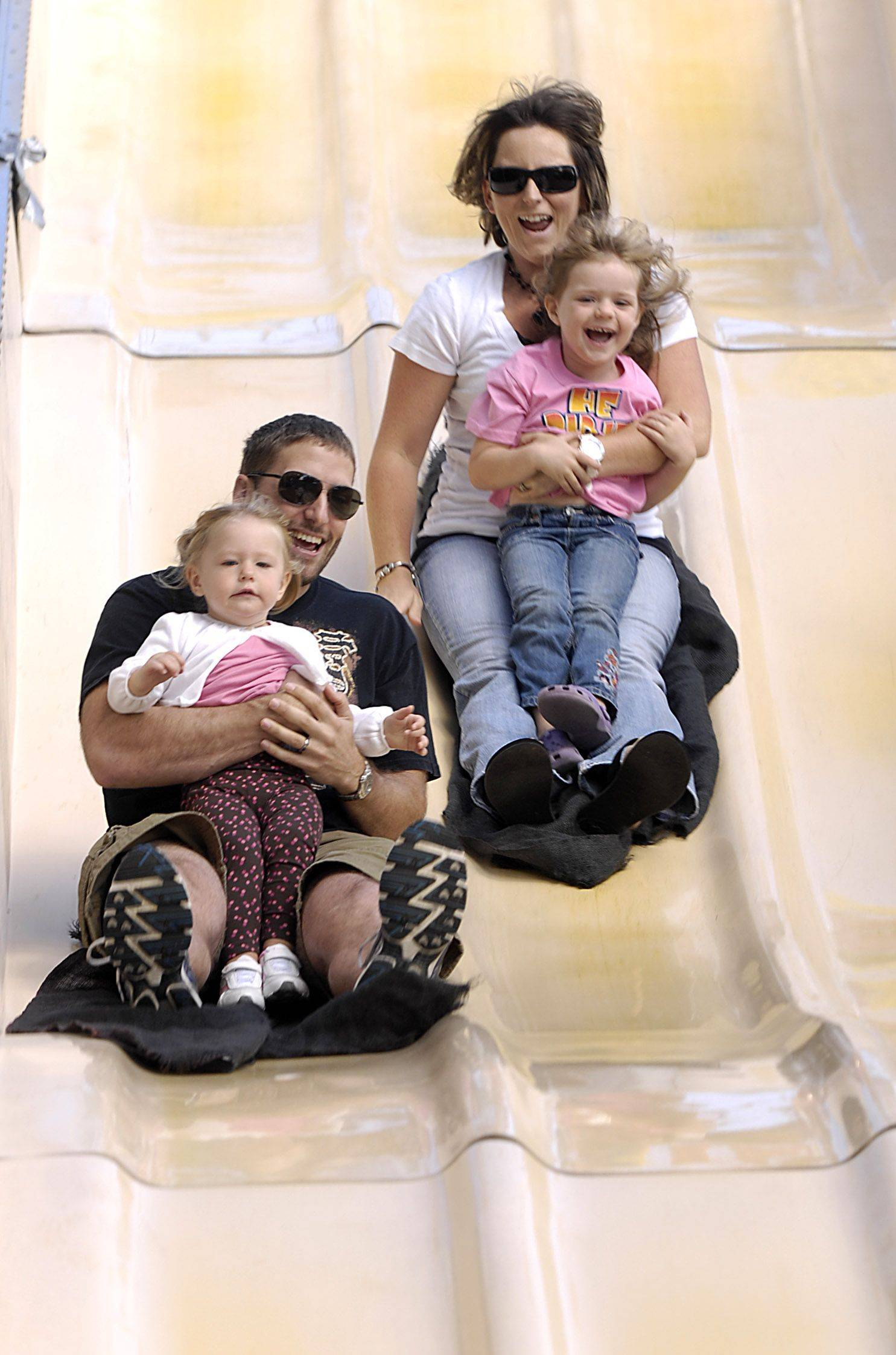 Scott Hecht and daughter Adalyn, 2 along with his wife Meagan Hecht and their niece Ryann Furlow, 4 of Naperville enjoy a trip down the Fun Slide at the Last Fling carnival in Naperville.