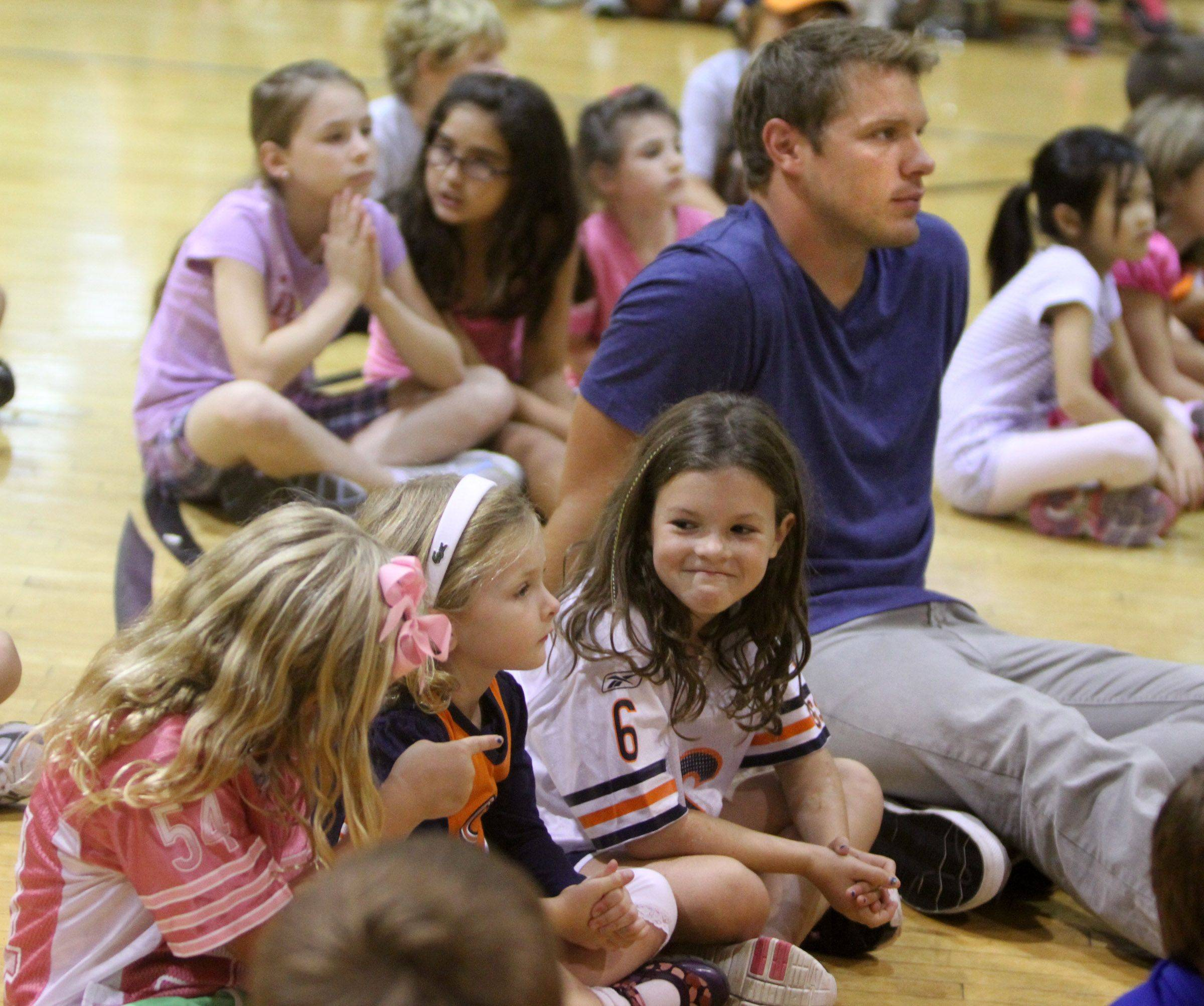 Macy Goodman, 7, wearing a Jay Cutler jersey, is all smiles as her friend Cameran Mather, 7, points out that Macy is sitting next to the Bears' Caleb Hanie during a clinic on nutrition and staying active Tuesday at Midtown Athletic Club in Palatine.