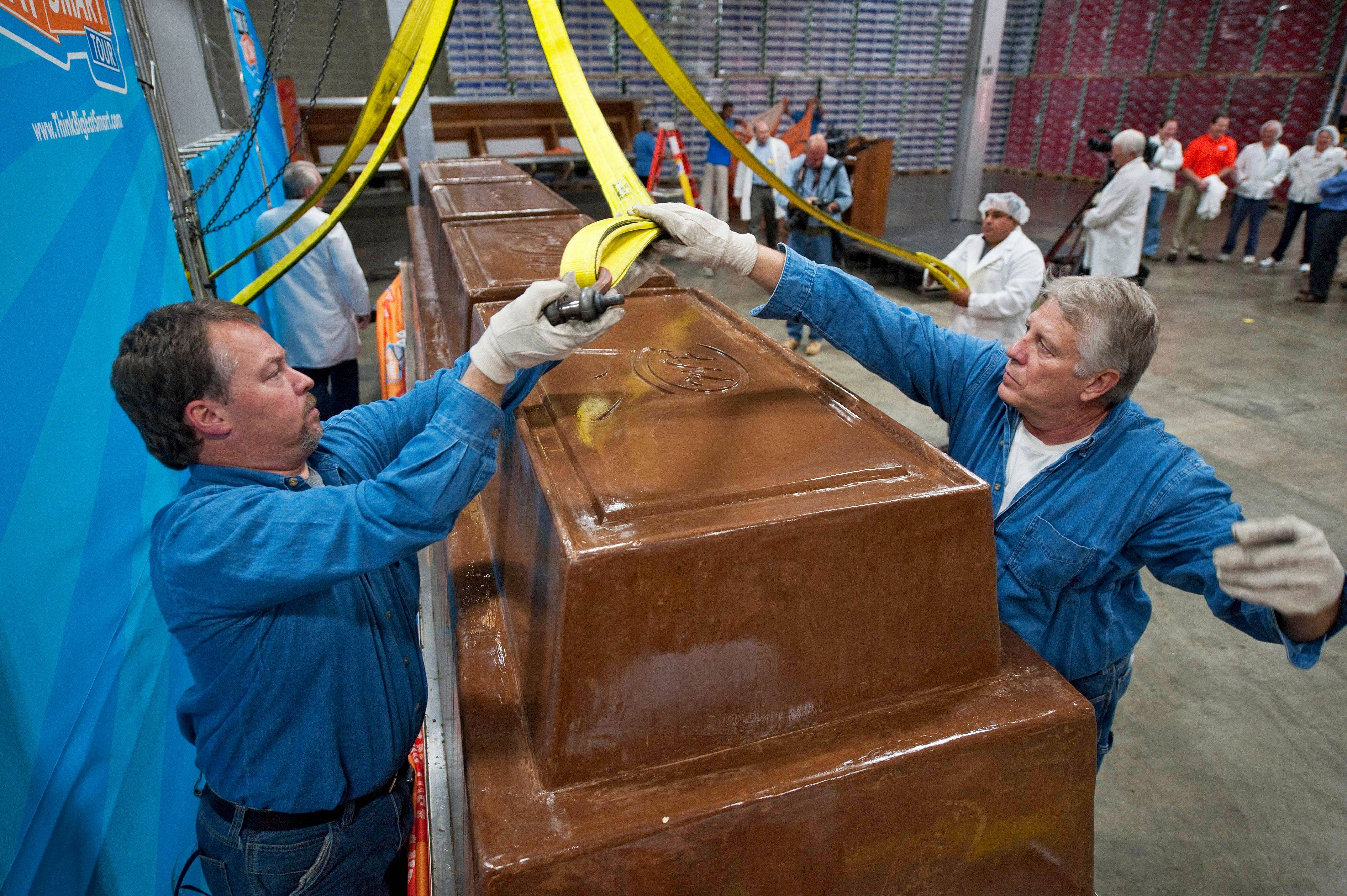 Garry Hine, left, and Gary Wychocki help move a giant chocolate bar to a scale Tuesday in Chicago. The chocolate bar weighs 12,000 pounds and includes 1,200 pounds of almonds, 5,500 pounds of sugar, 2,000 pounds of milk powder, 1,700 pounds of cocoa butter and 1,400 pounds of chocolate liquor.