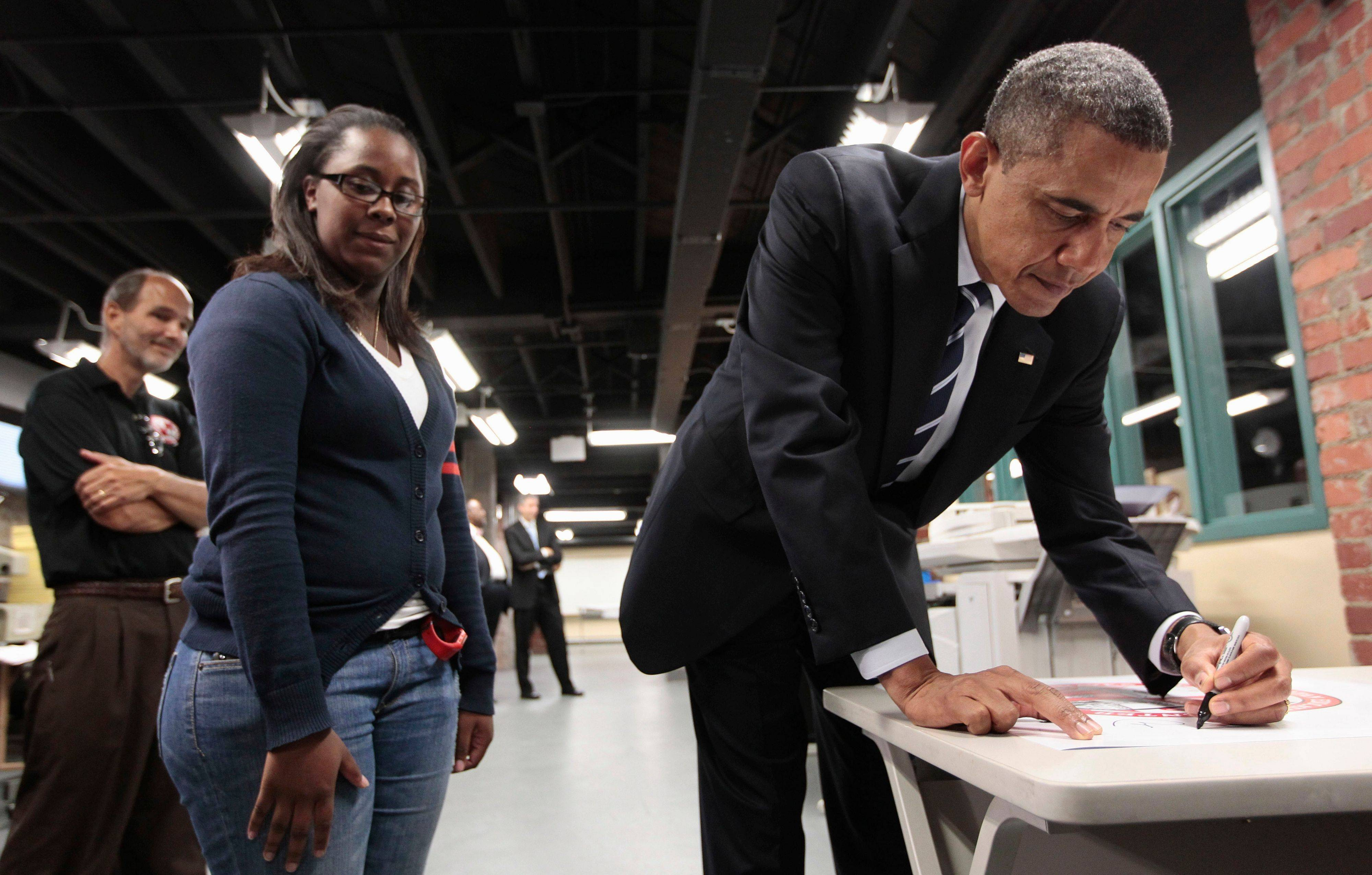 President Barack Obama signs a school poster as he tours classrooms with teacher Keith Morefield, left, Tuesday at Fort Hayes Arts and Academic High School in Coumbus, Ohio.