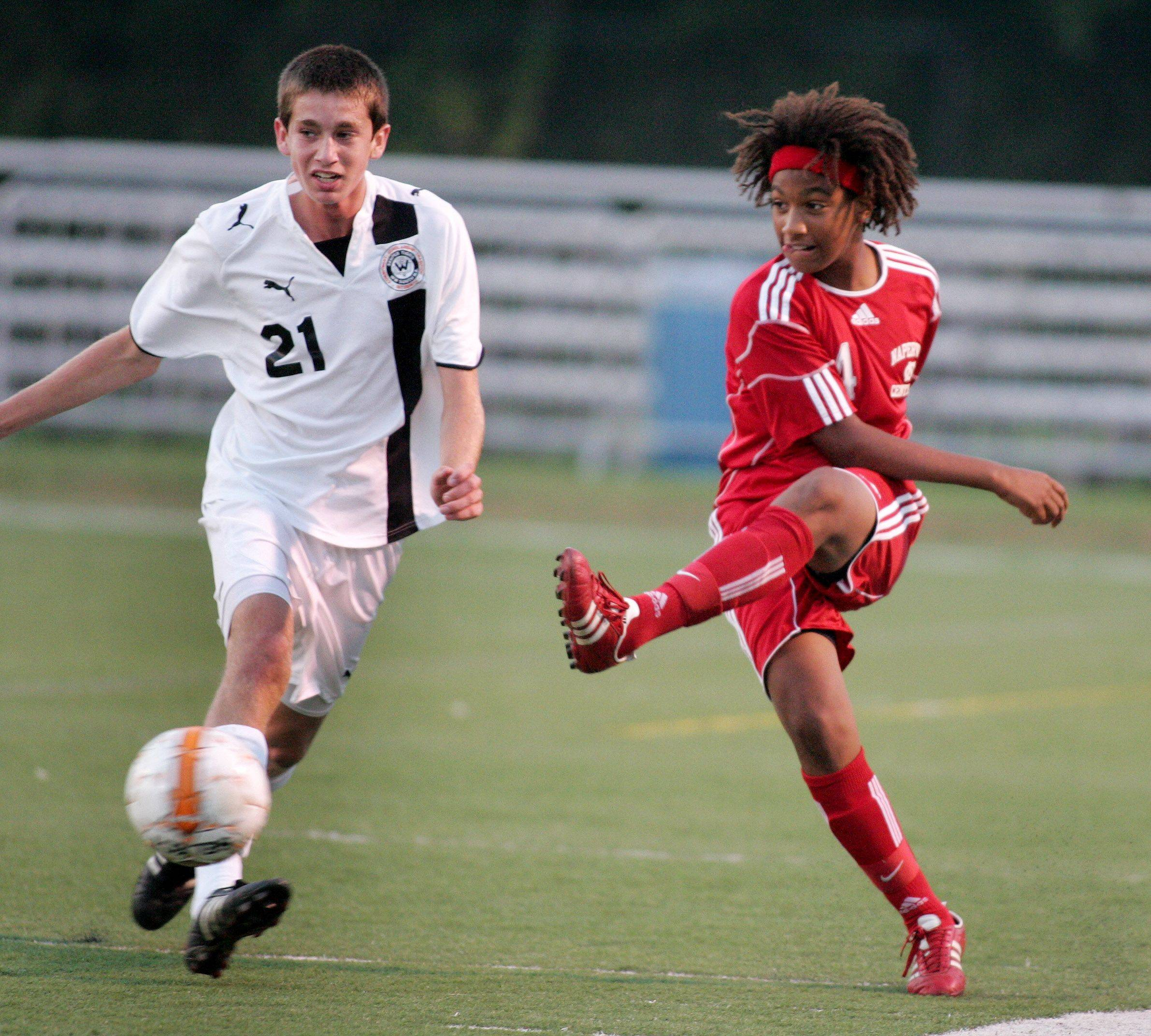 Bev Horne/bhorne@dailyherald.com Jay Tegge, right, of Naperville Central, kicks the ball away from Max Carey, left, of Wheaton Warrenville South during boys soccer action Tuesday in Wheaton.