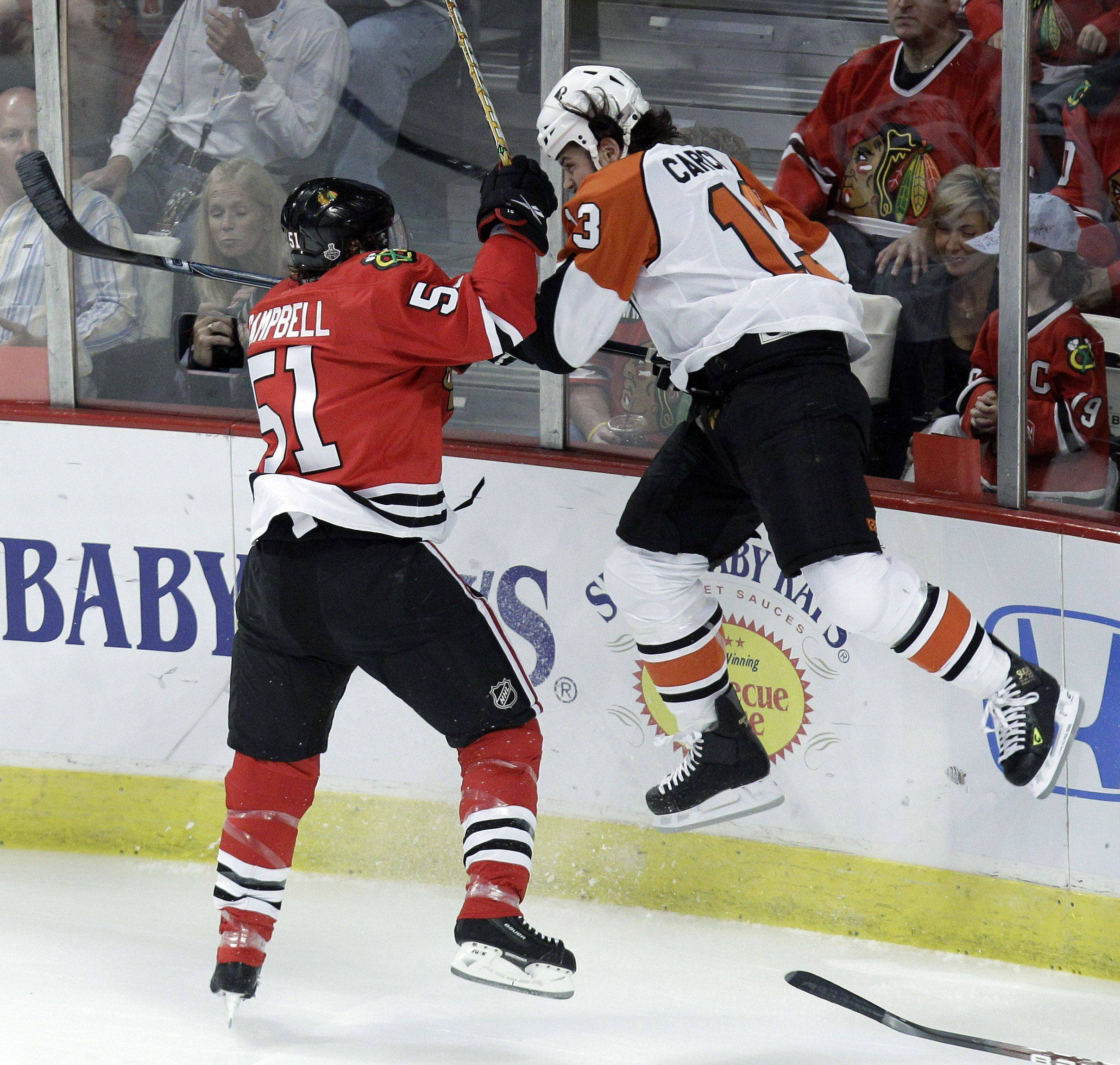 Blackhawks defenseman Brian Campbell (51) checks Philadelphia Flyers left wing Daniel Carcillo (13) into the boards in the first period of Game 2 of the Stanley Cup NHL hockey in 2010.