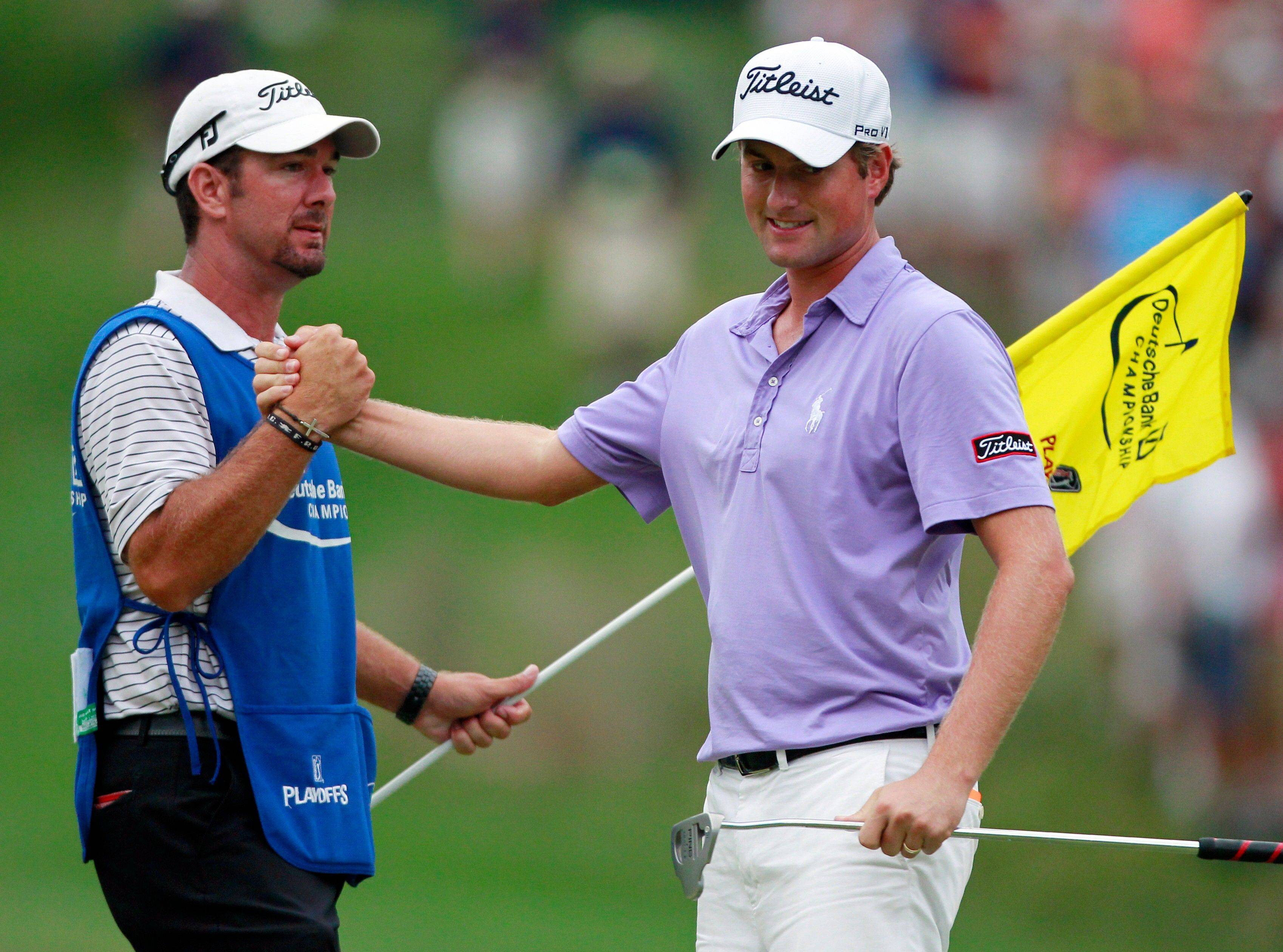 Webb Simpson, right, celebrates with his caddie Paul Tesori after winning against Chez Reavie with a birdie on the second playoff hole in the final round of the Deutsche Bank Championship golf tournament at TPC Boston in Norton, Mass.