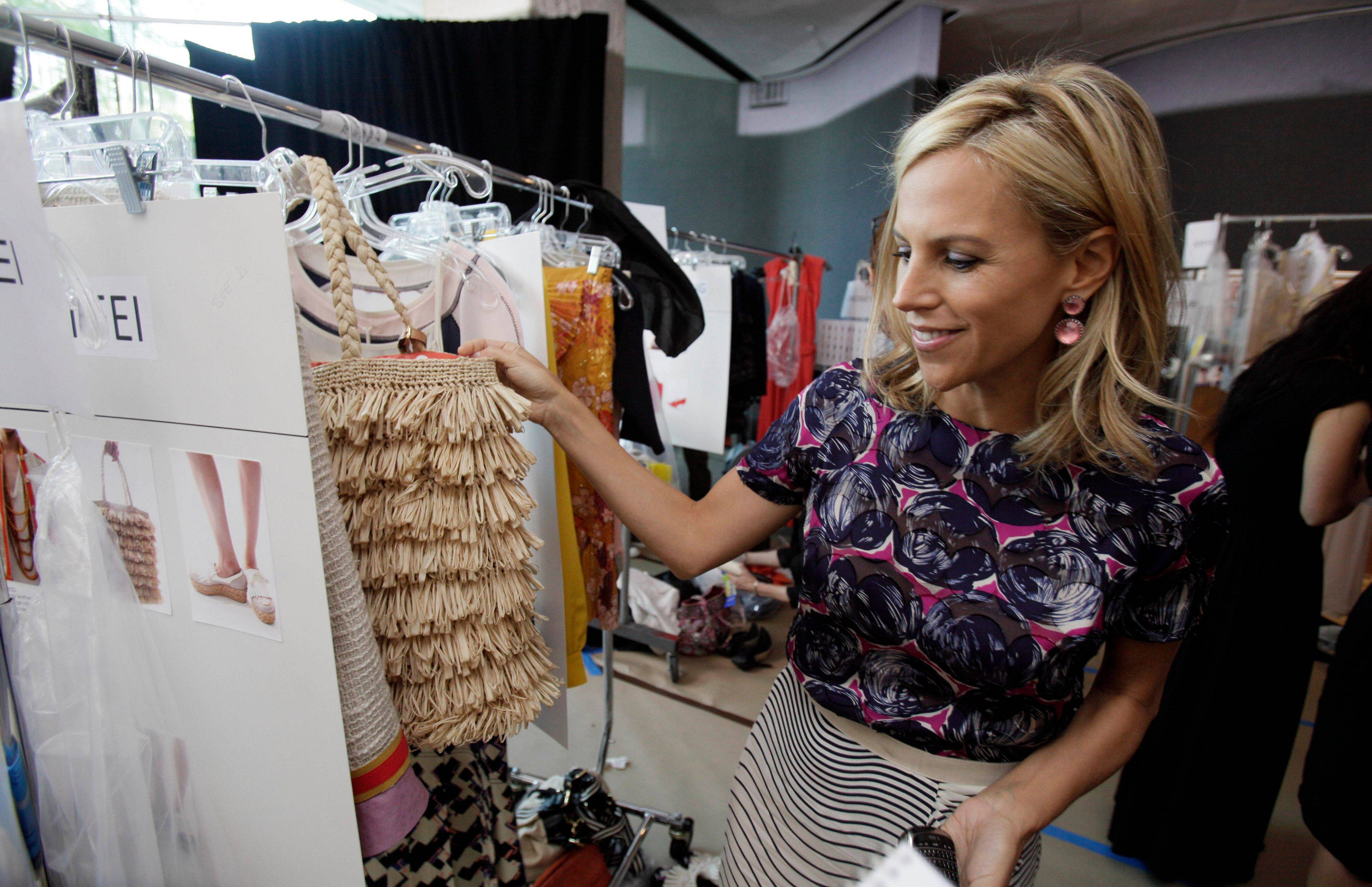 Designer Tory Burch looks over her designs backstage before her spring 2012 collection is modeled during Fashion Week in New York, Tuesday, Sept. 13, 2011.