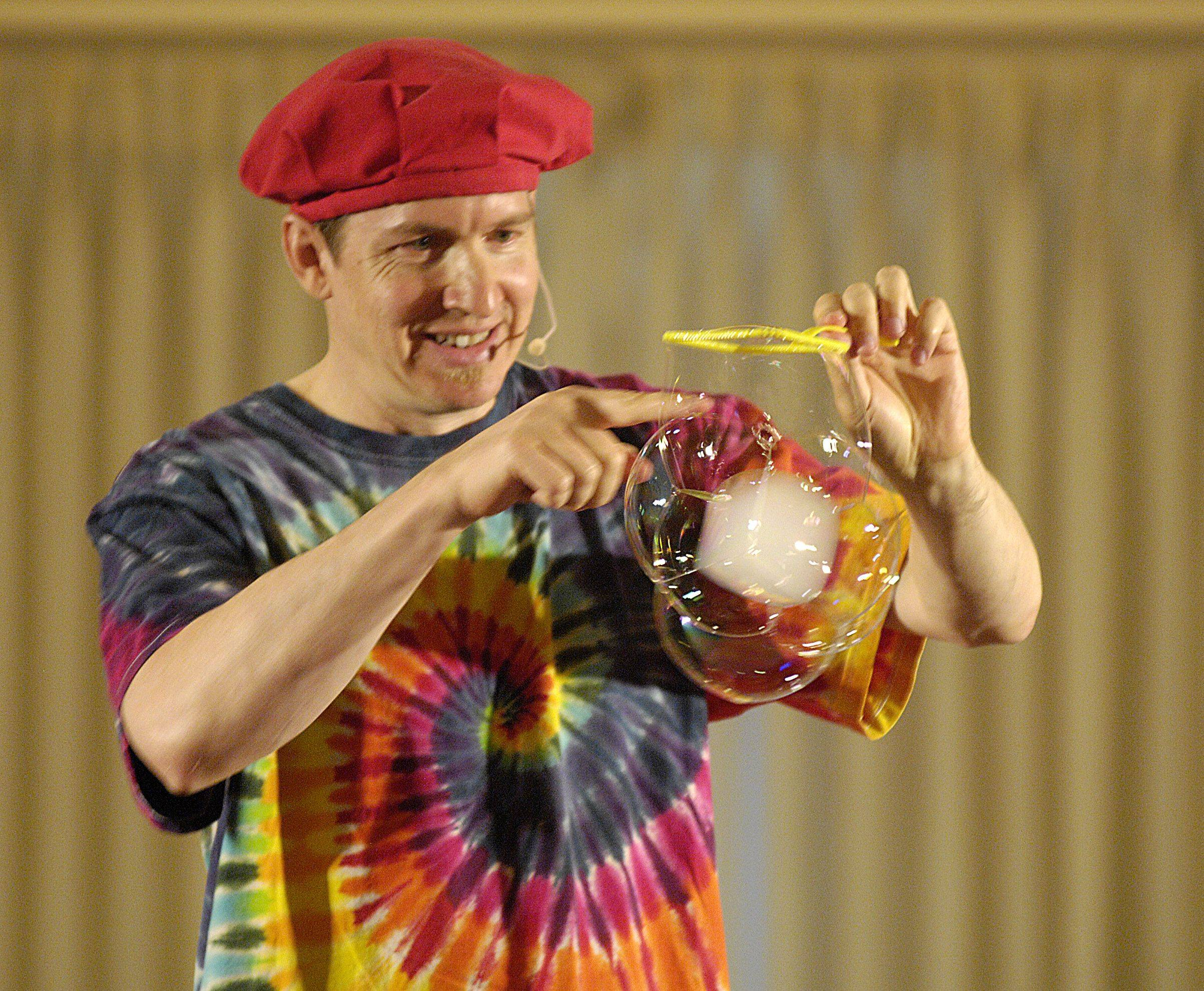 Geoff Akins of Bubble Wonders makes a square bubble while performing for teachers and parents at the Premier Showcase of school assembly performers Tuesday in Lombard.