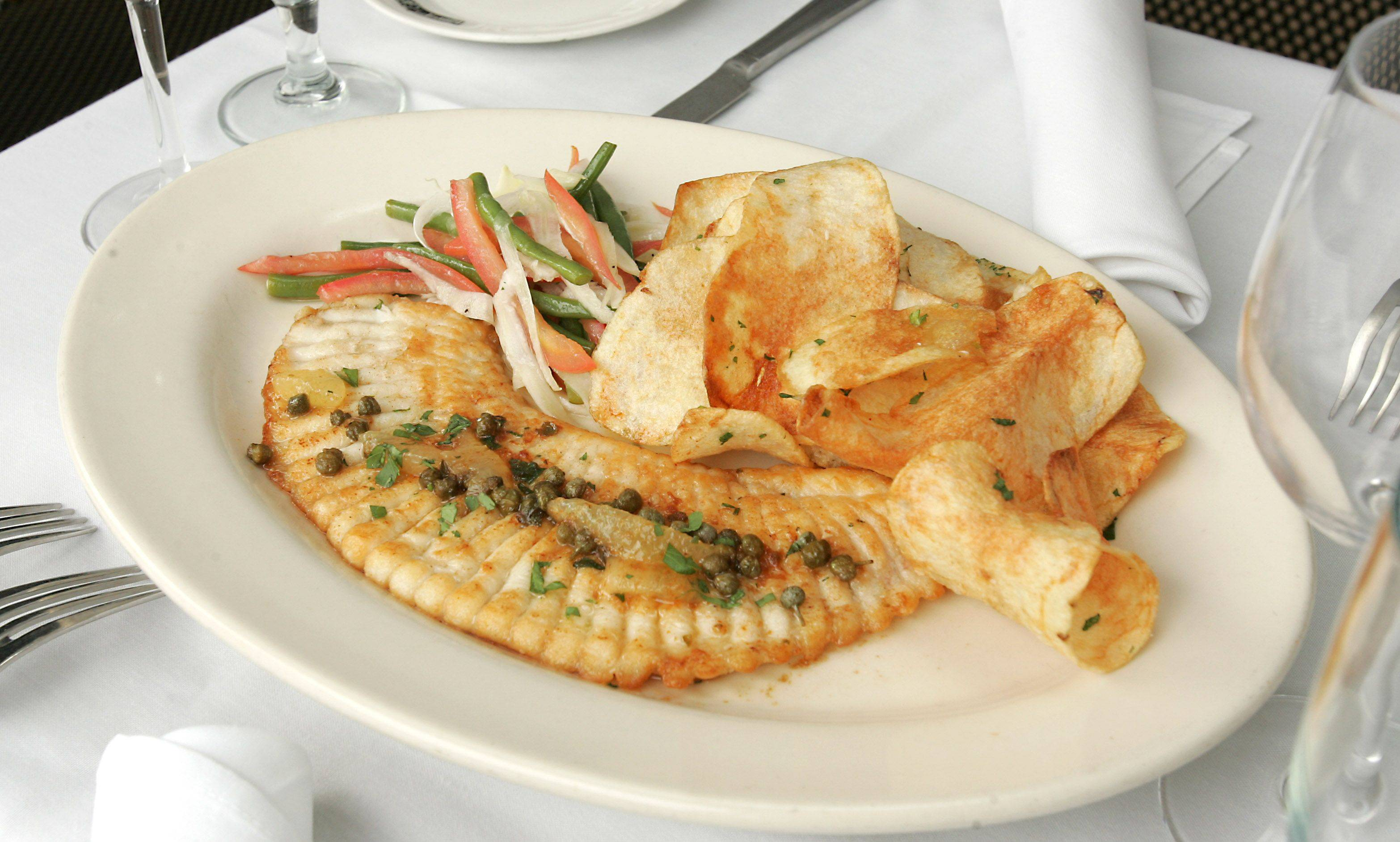 Chef Bruce Williams serves skate wing with garlic potato chips and summer salad to diners at Mon Ami Gabi Restaurant in Oak Brook.